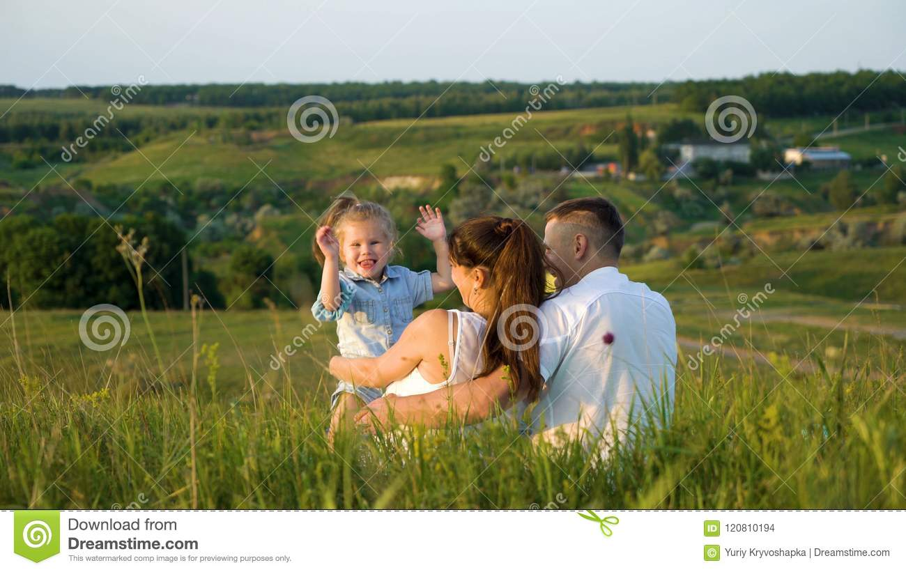 Pregnant couple with toddler daughter have leisure time outdoors back view