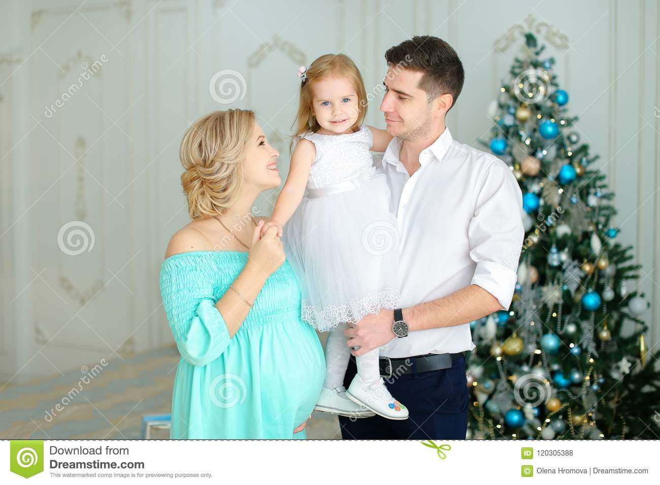 Pregnant european woman standing near husband keeping little daughter near Christmas tree.