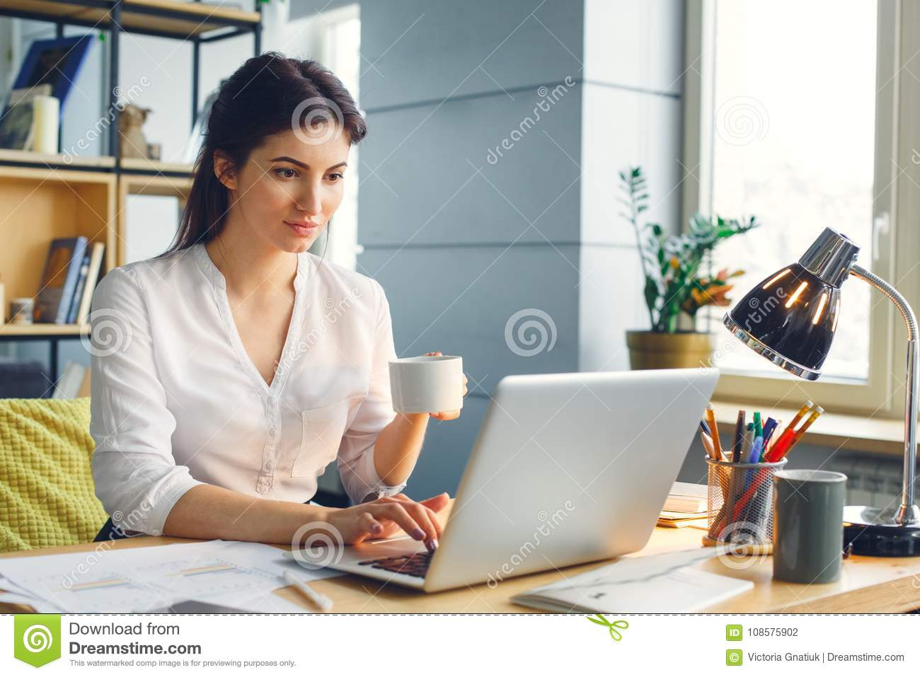 Pregnant business woman working at office motherhood sitting browsing laptop drinking coffee