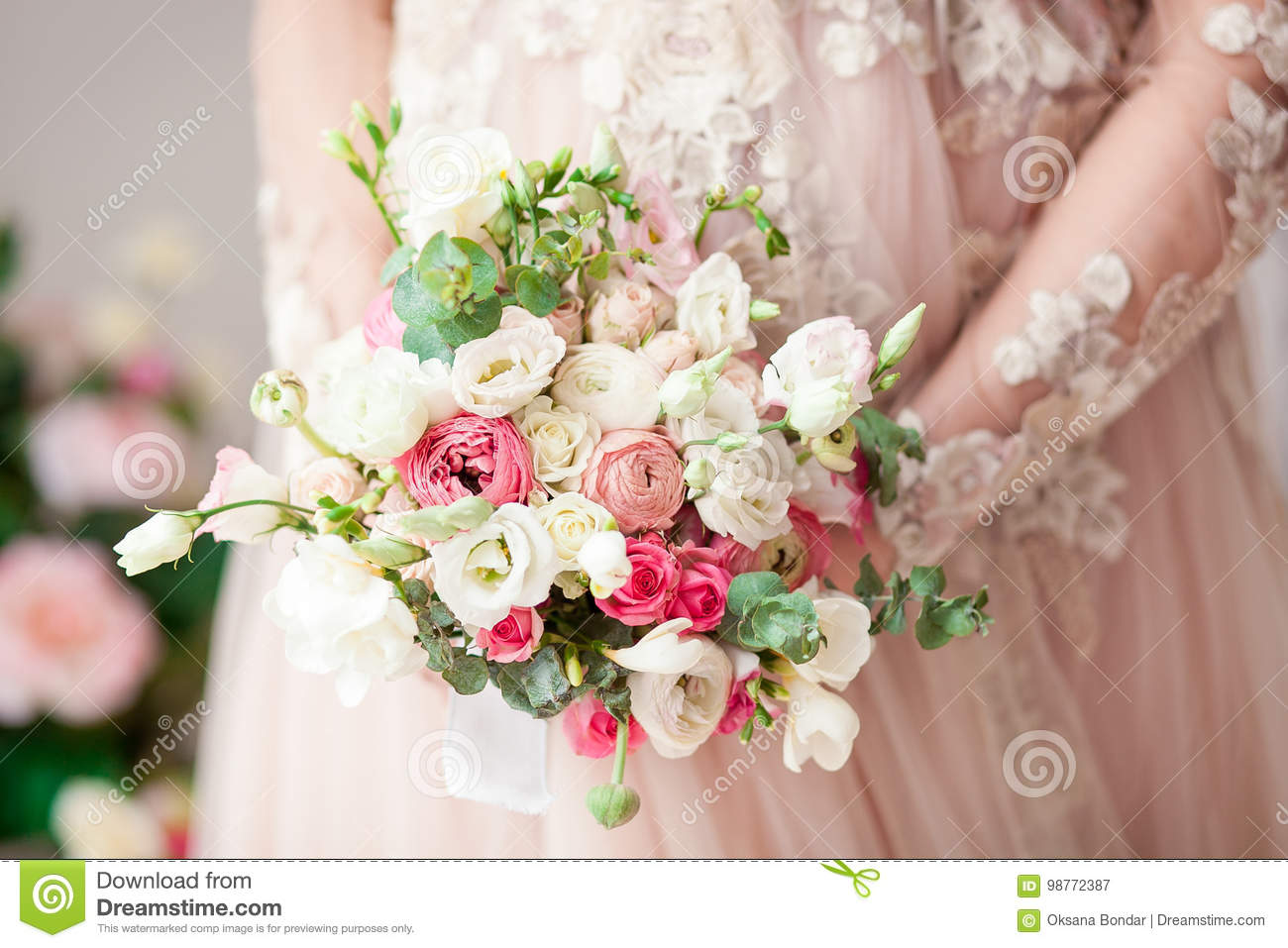 Pregnant girl in a beige dress with a bouquet in hands. Natural. Waiting for a miracle.
