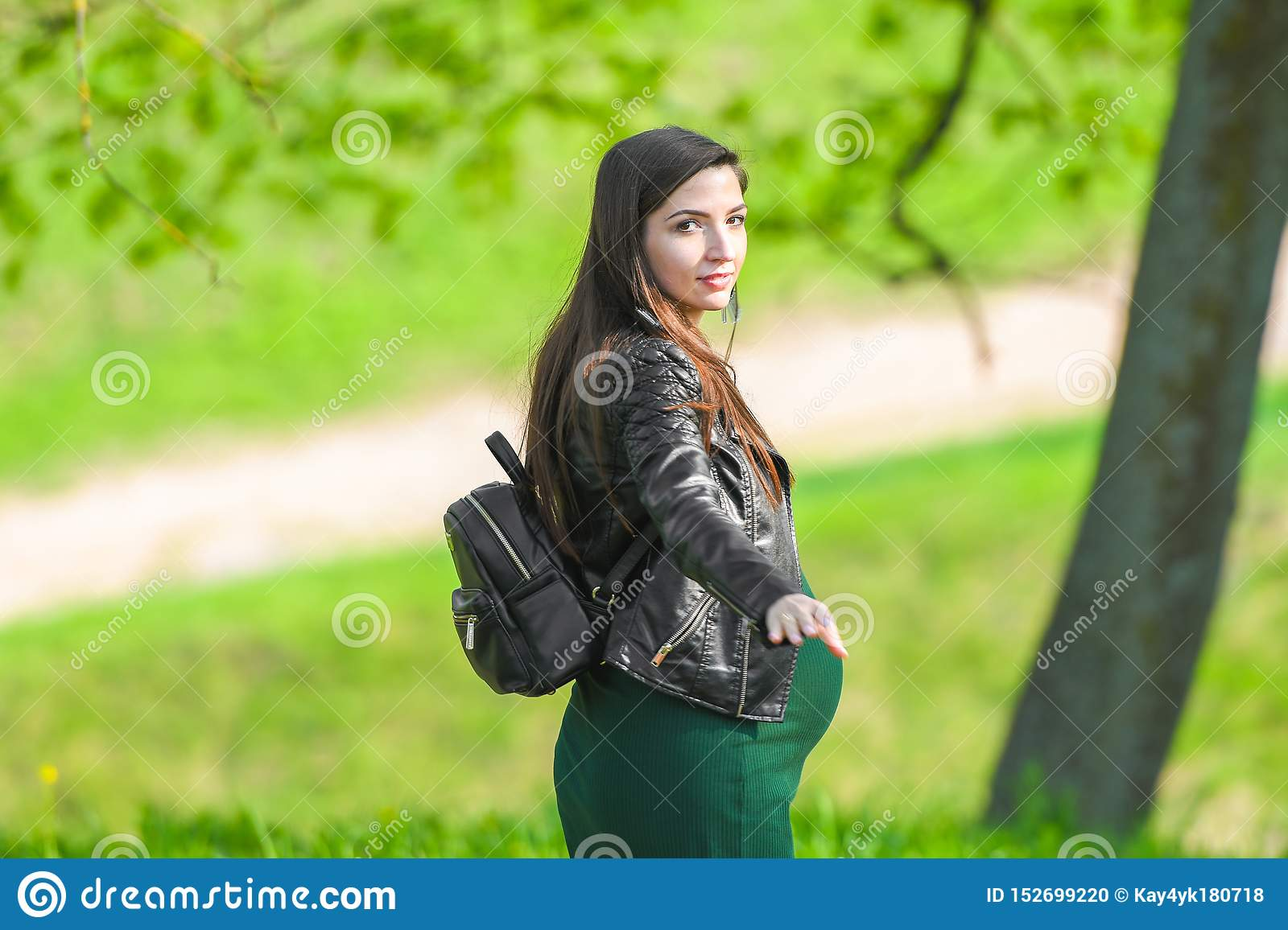 Pregnant girl enjoys life. portrait of a beautiful pregnant woman. The happy lady smiled and was delighted. Arms outstretched and