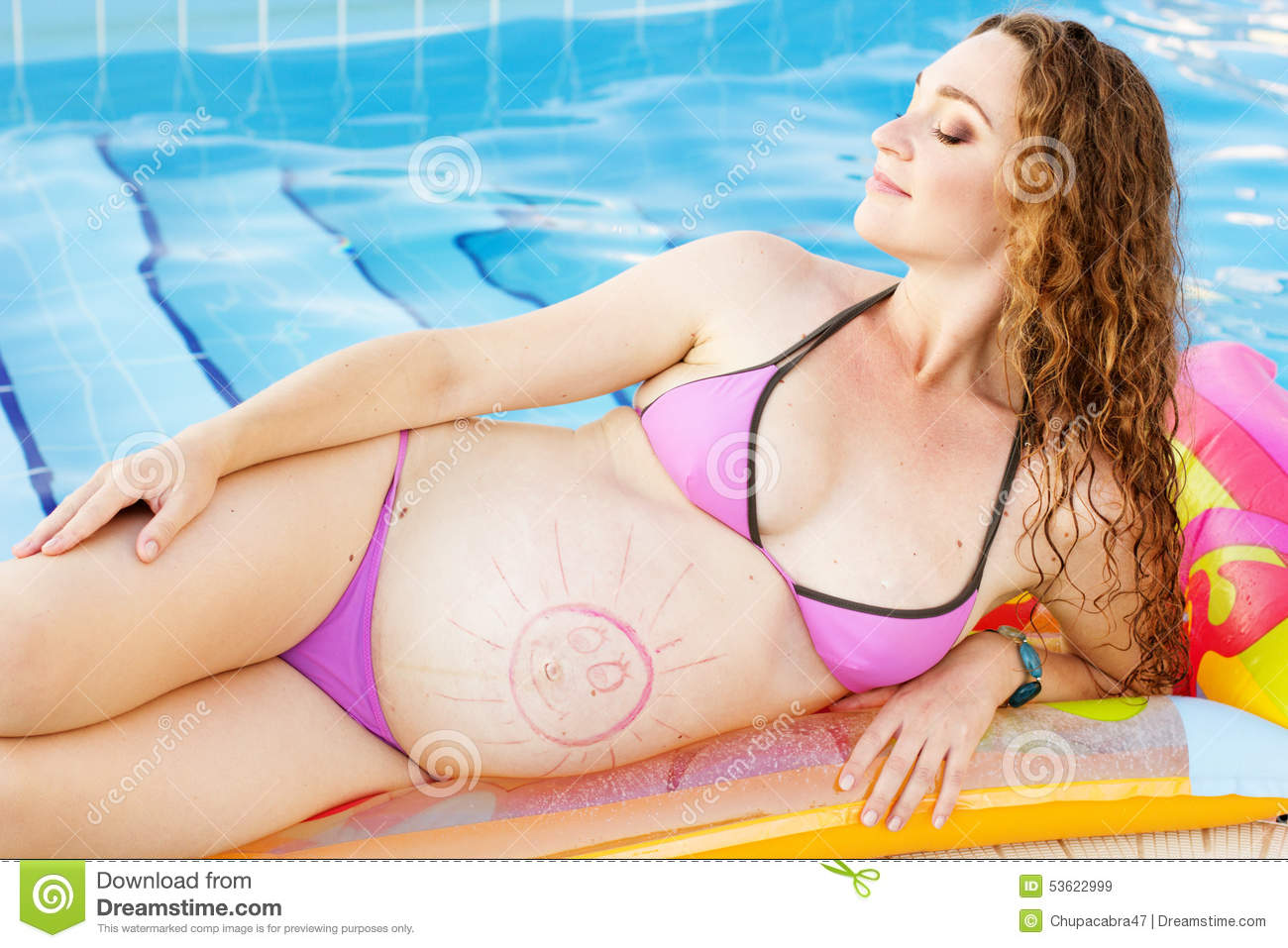 bd66951a56425 Beautiful pregnant woman is wearing swimsuit is lying and resting on colorful  mattress near swimming pool with blue water, vacations