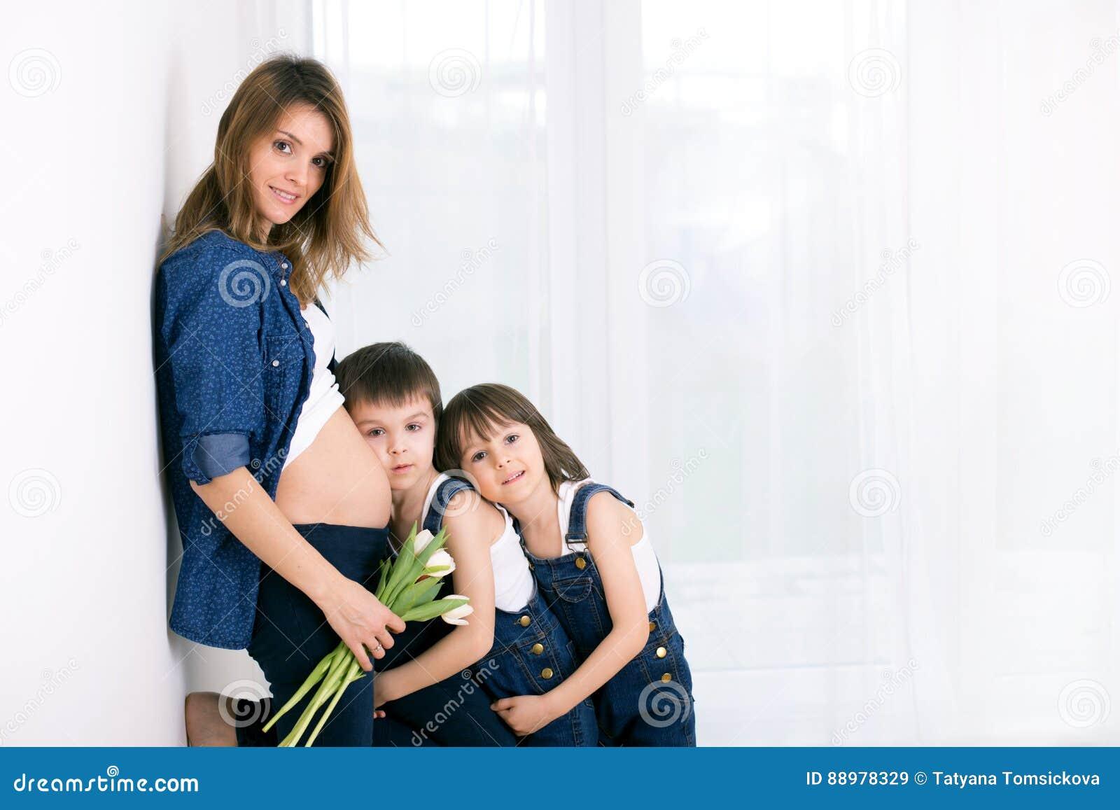 Pregnant mother, hugging her children, receiving tulips, flowers