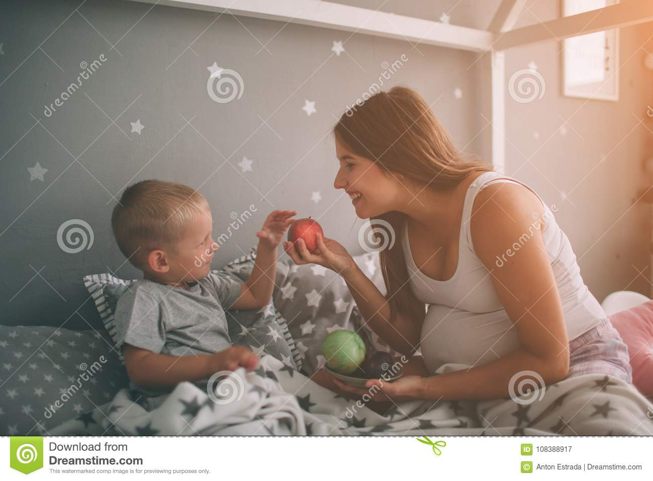 Pregnant mother and little boy son are eating an apple and peach in the bed t home in the morning. Casual lifestyle in