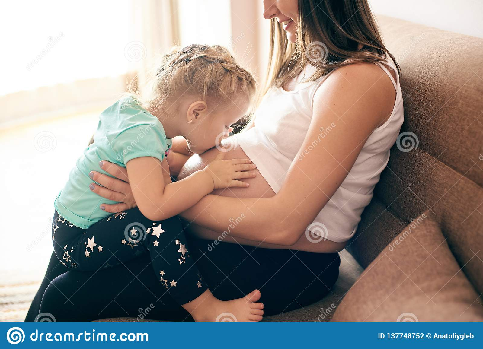 Pregnant mother sitting with cute daugher kissing big belly