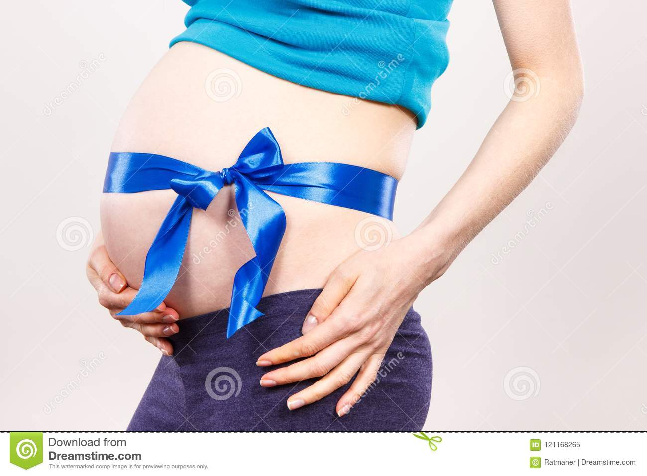 Pregnant woman with blue ribbon, concept of expecting for newborn