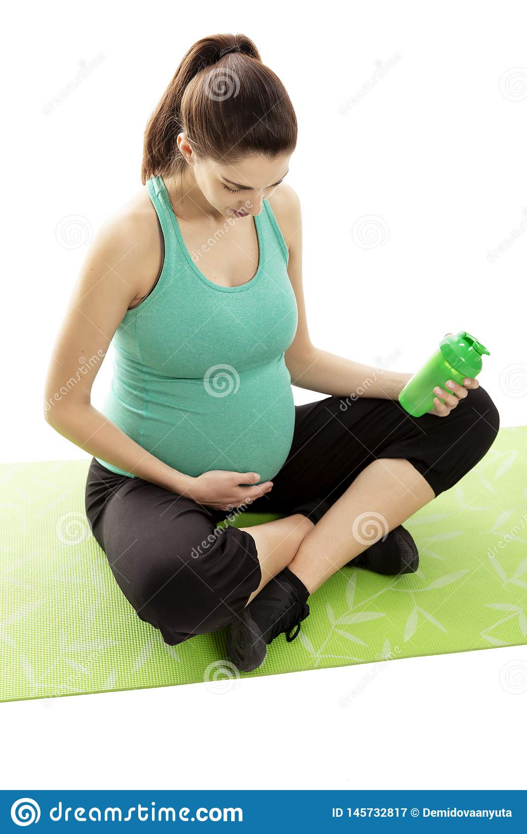 Pregnant woman, brunette, is engaged in fitness on the mat. In the hands of a bottle of water.