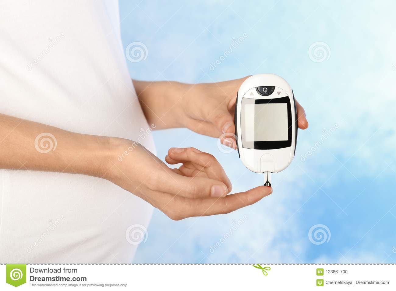 Pregnant woman checking blood sugar level with glucometer on color background. Diabetes test