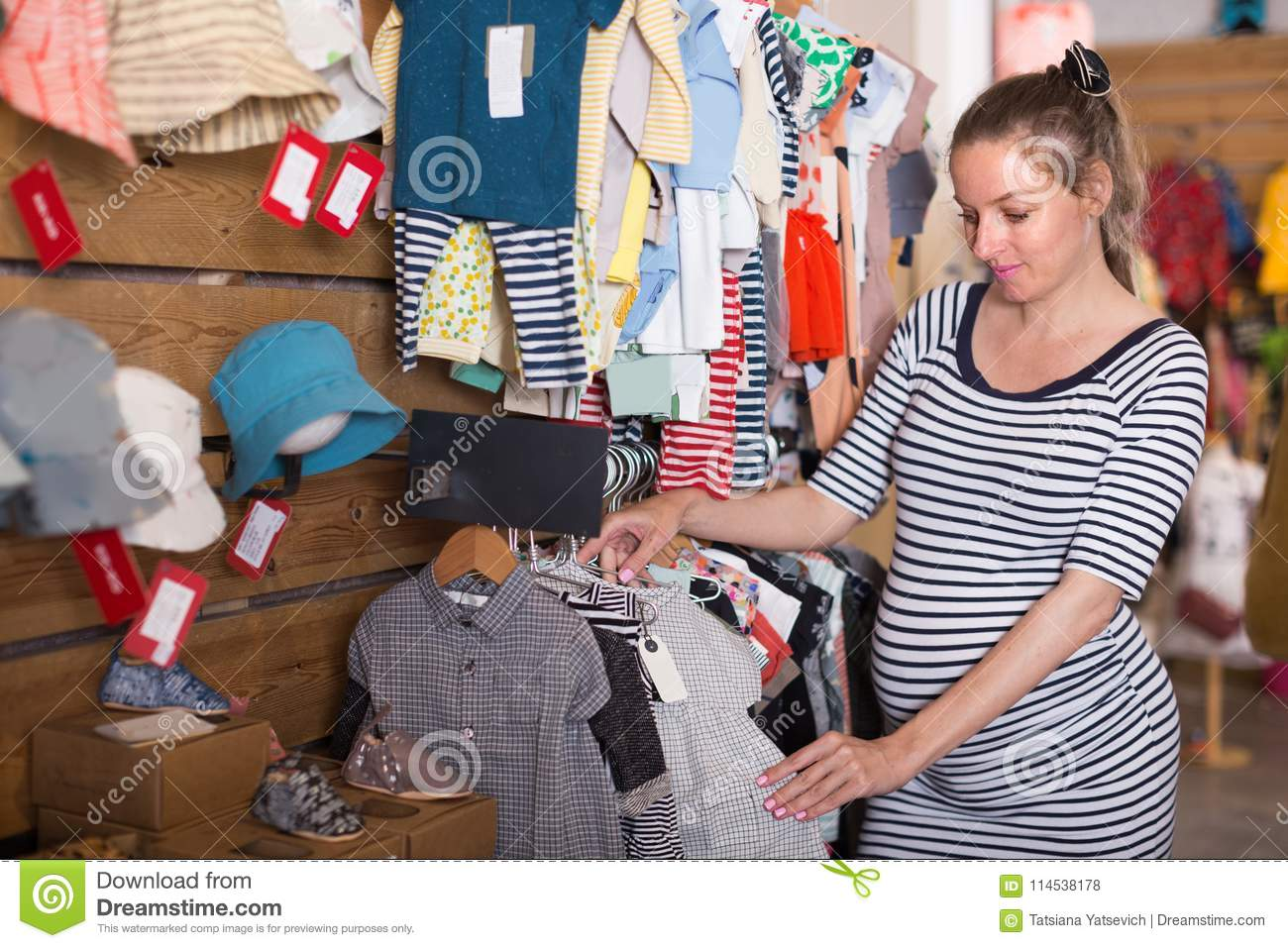 6ddae086d713f Pregnant Woman Chooses Clothes For The Future Child In Store Stock ...