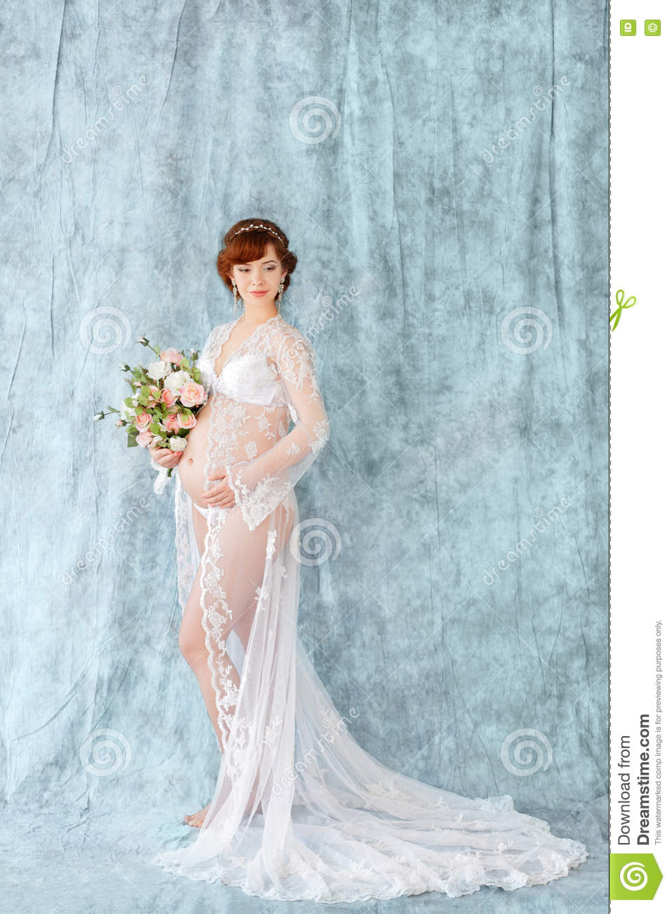 Pregnant Woman Holding Flowers, Standing In The Boudoir Dress On A ...
