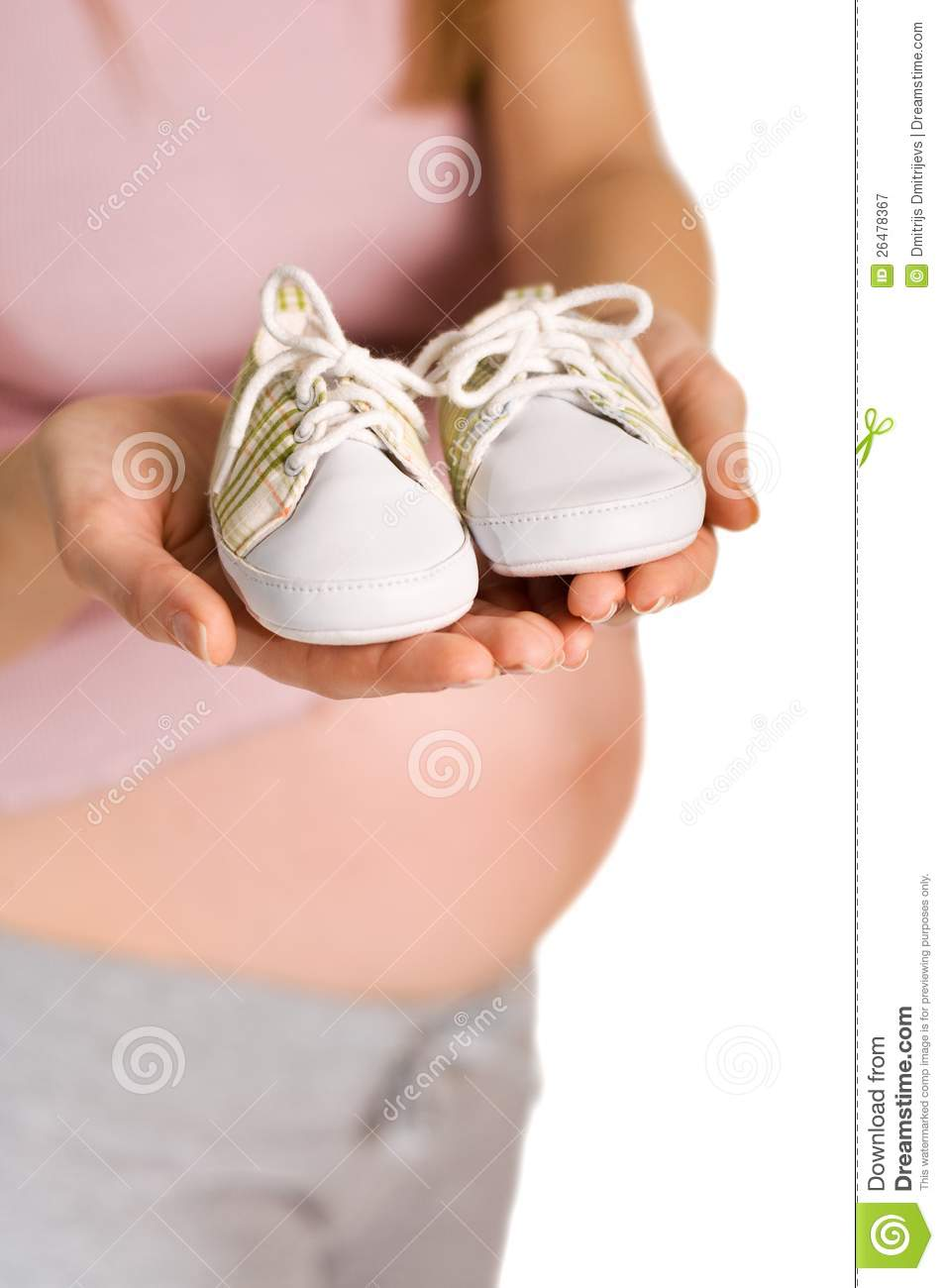 Pregnant woman holding pair of white shoes for baby (Shallow dof