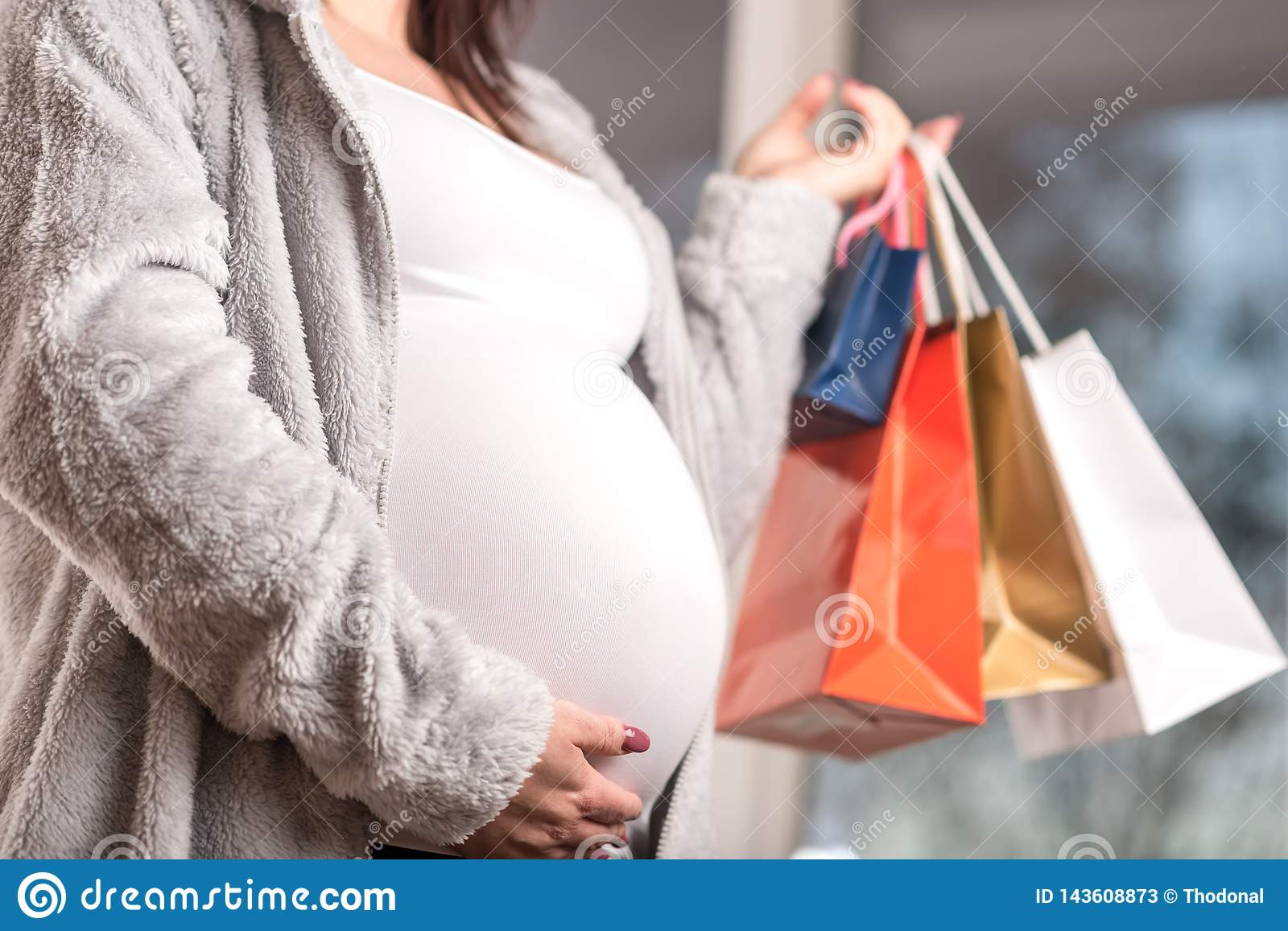 Pregnant woman with shopping bags touching her belly