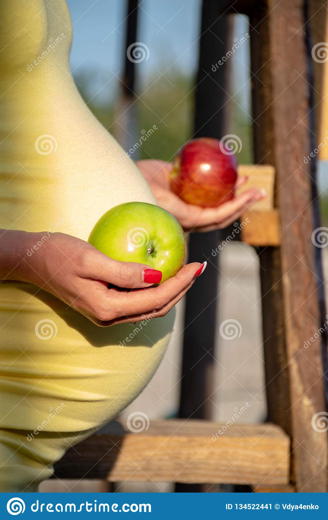 A pregnant woman holds an apple in her hands