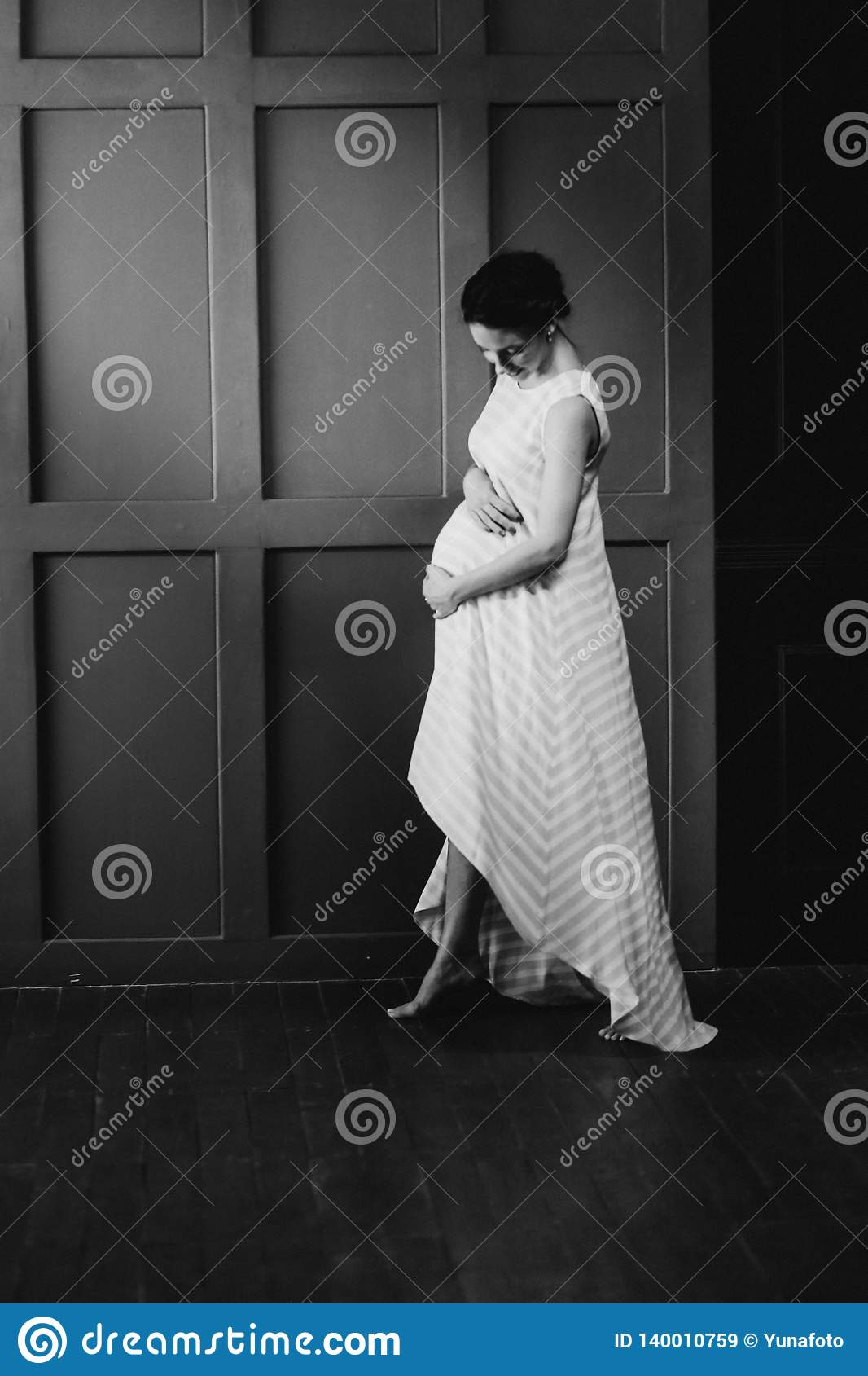 Pregnant woman inside room gently strokes belly