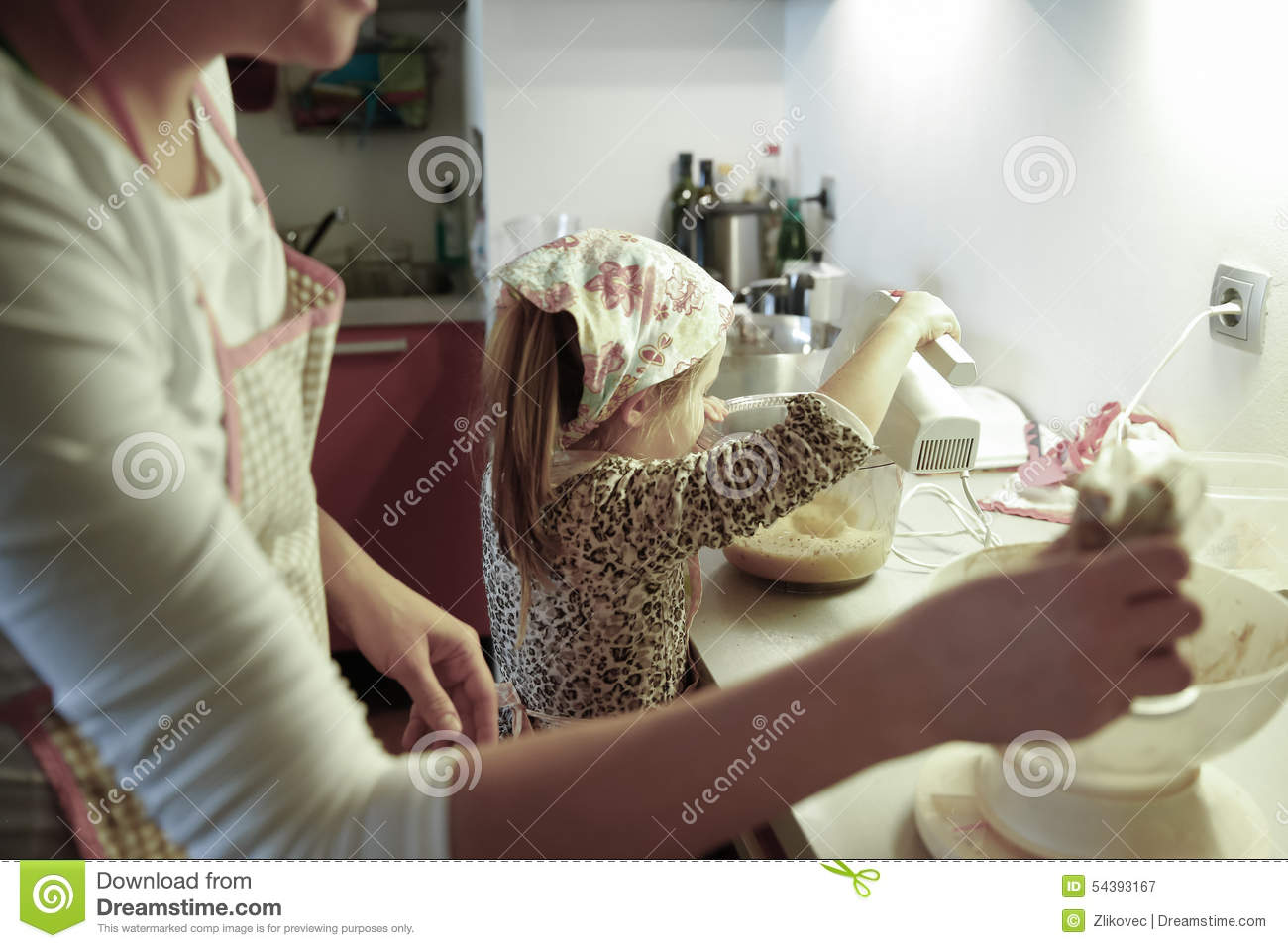 Pregnant woman and little girl cooking in the kitchen