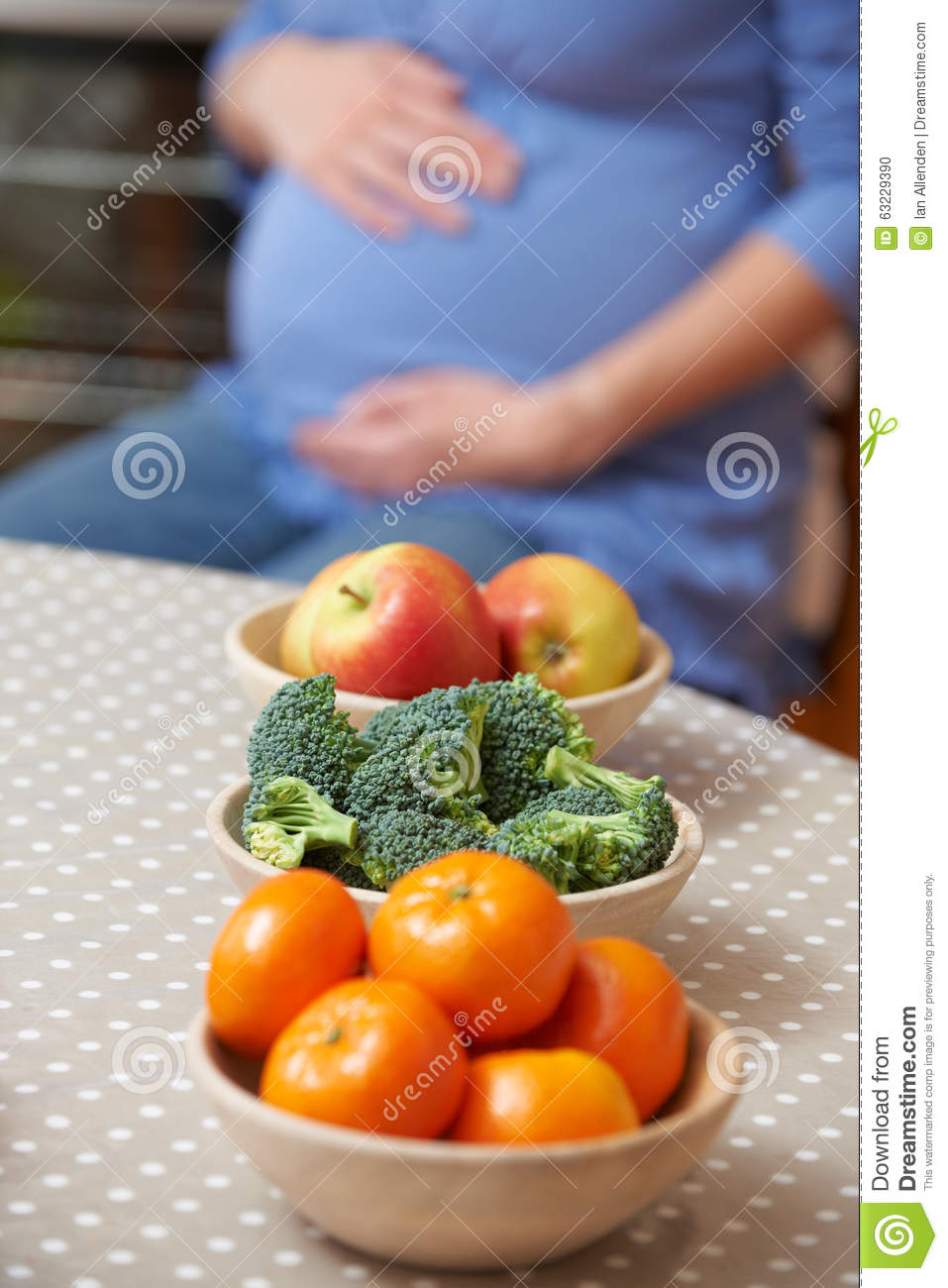 Pregnant Woman Looking At Bowls Of Healthy Fruit And Vegetables