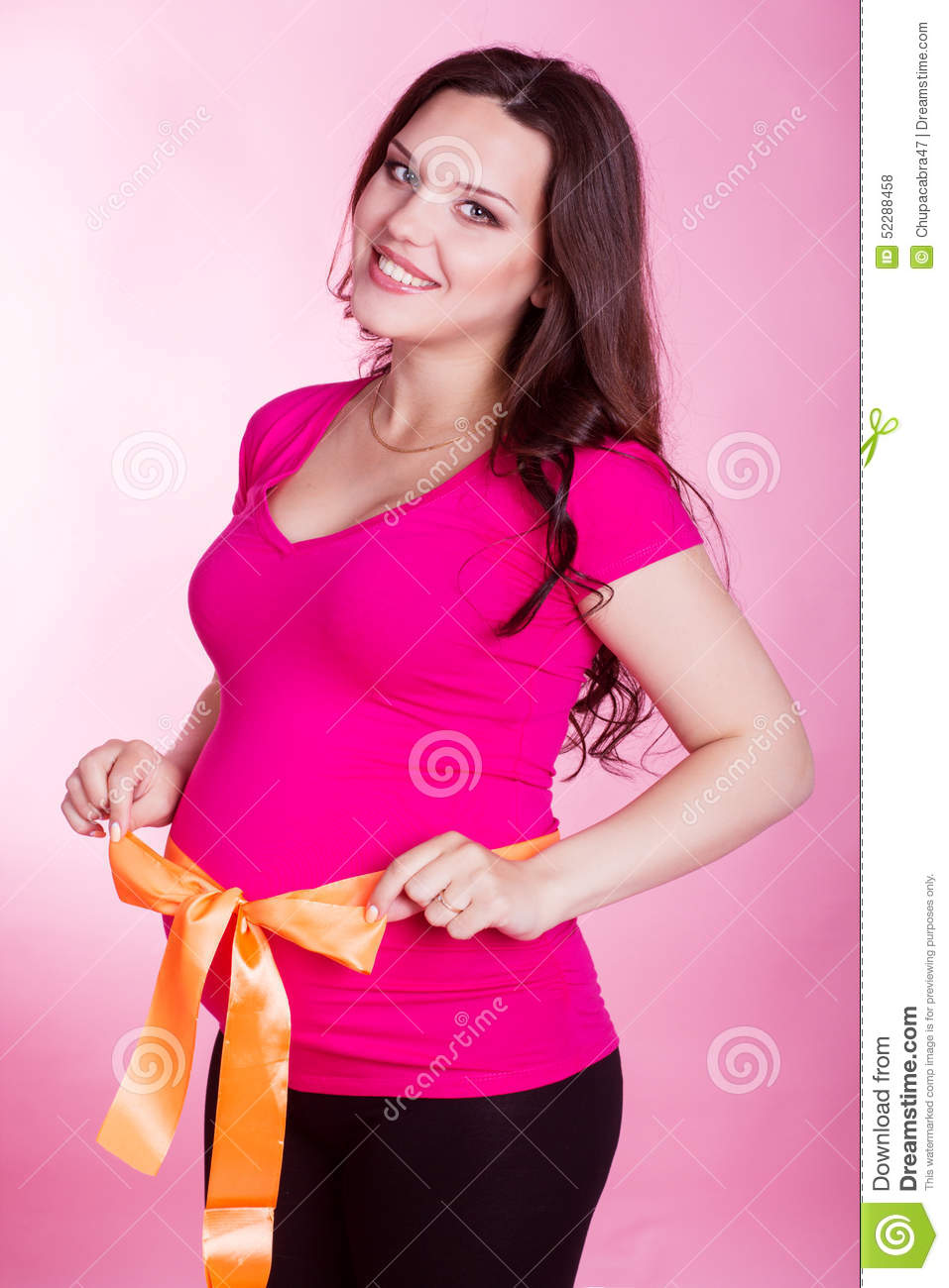 Pregnant woman with orange ribbon on her belly