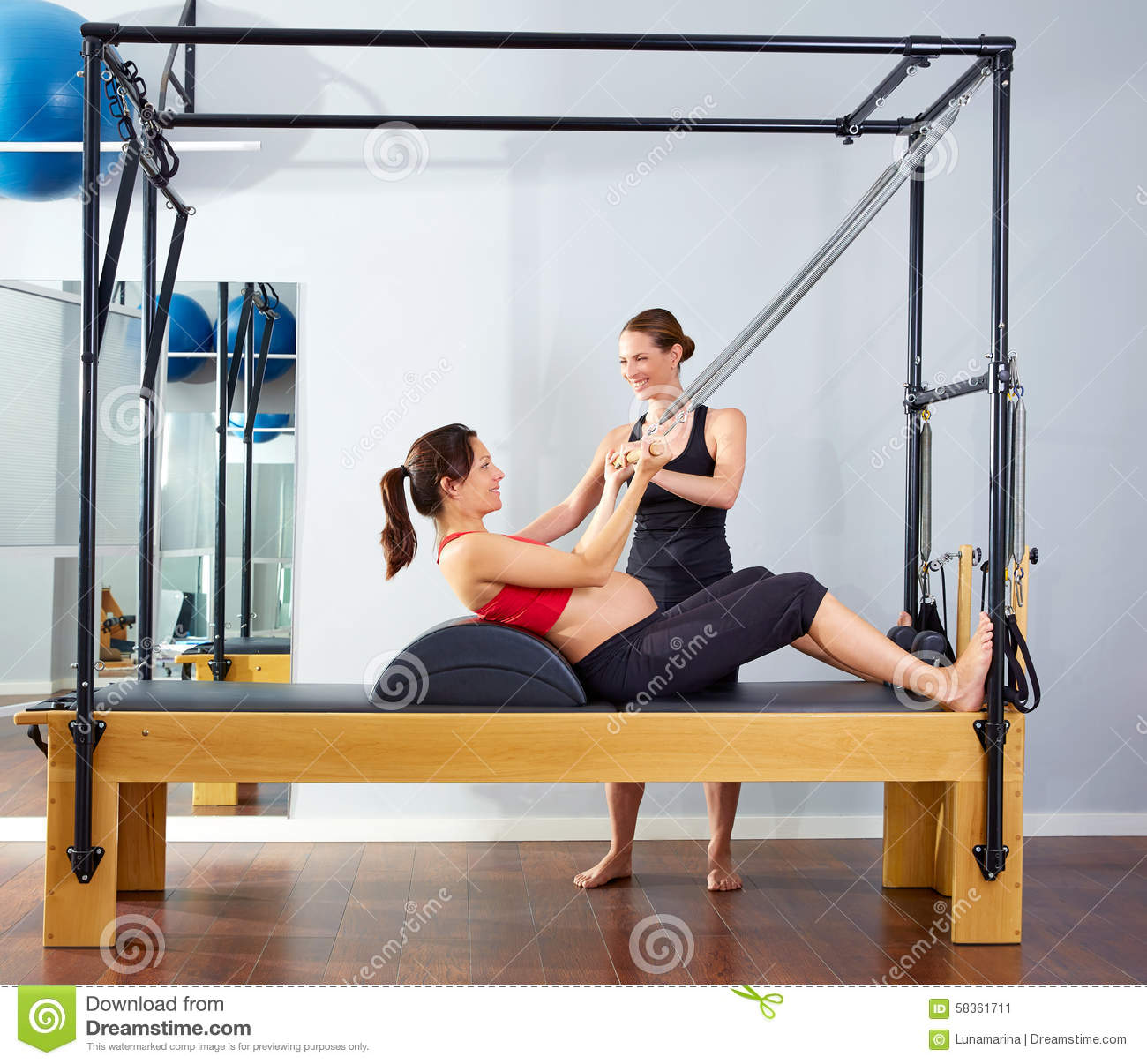 Cadillac Pilates: Pregnant Woman Pilates Reformer Roll Up Exercise Stock Photo