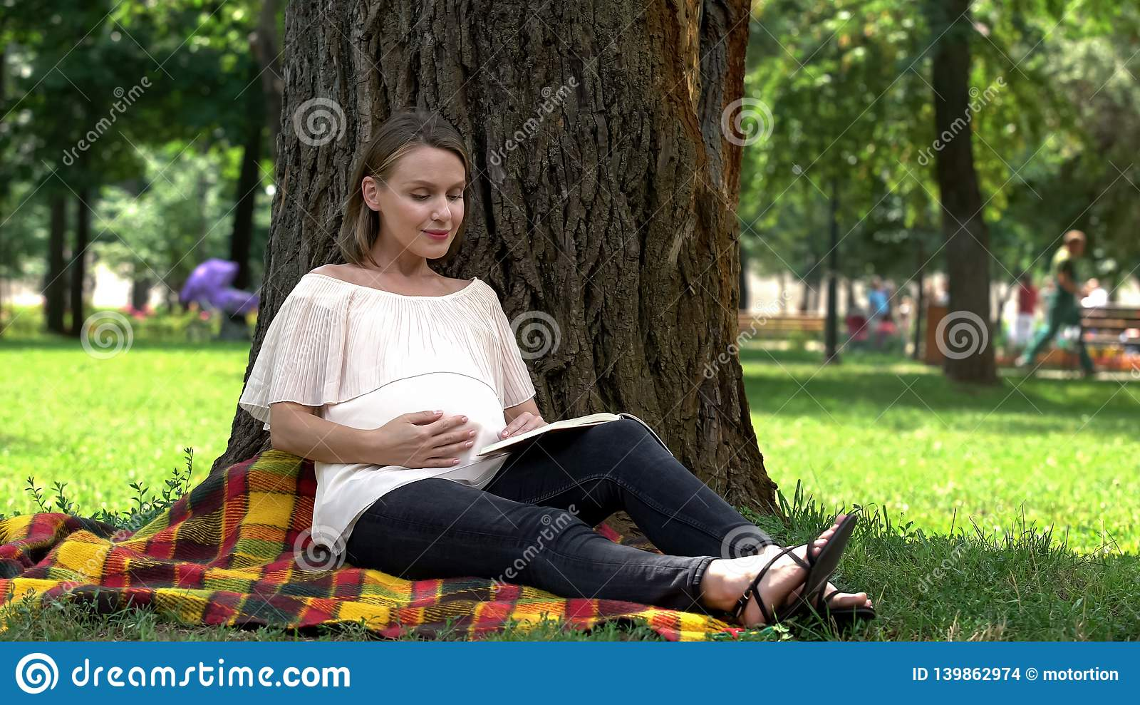 Pregnant woman reading book in park, relaxing outdoors, health and prenatal care