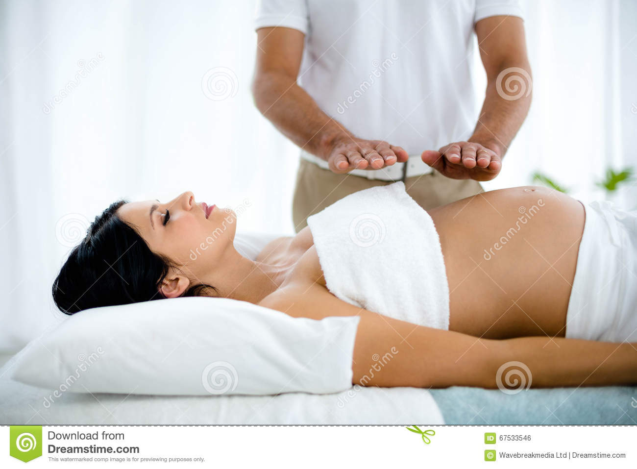 pregnant woman receiving a stomach massage from masseur stock photo image 67533546. Black Bedroom Furniture Sets. Home Design Ideas
