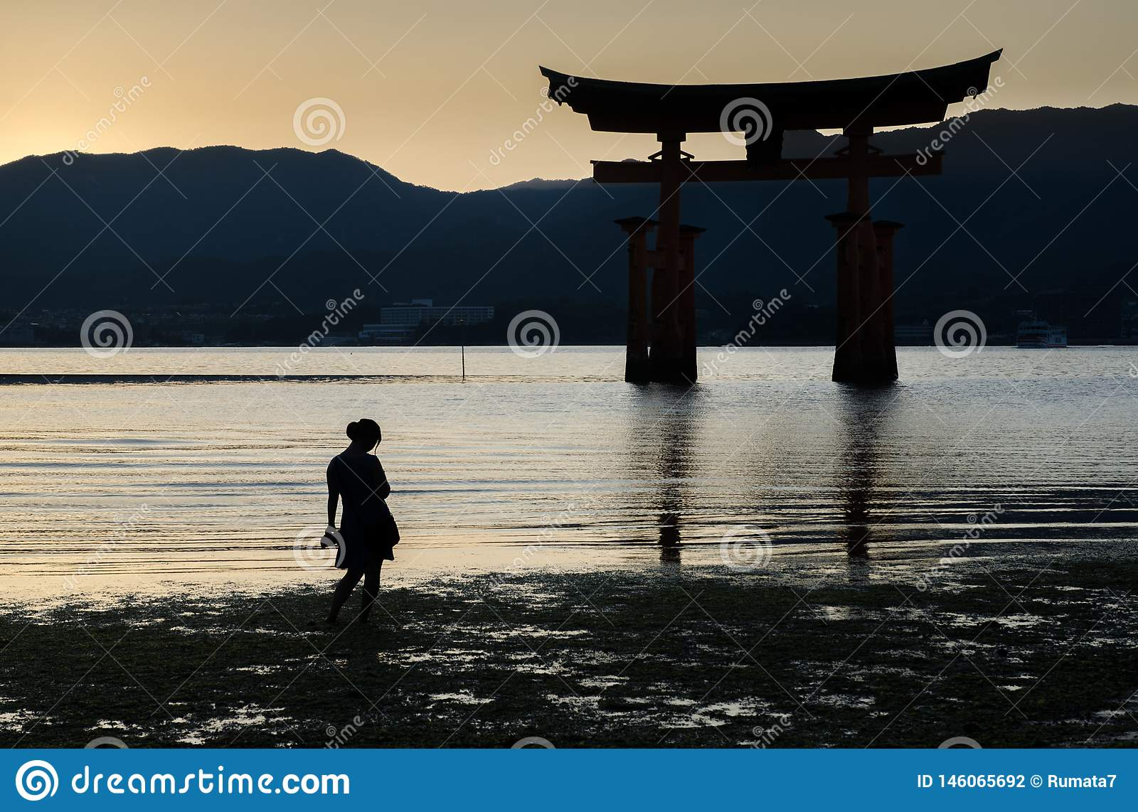 Pregnant woman silhouette near Torii -  floating gate of Miyajima (Itsukushima ) island at sunset time