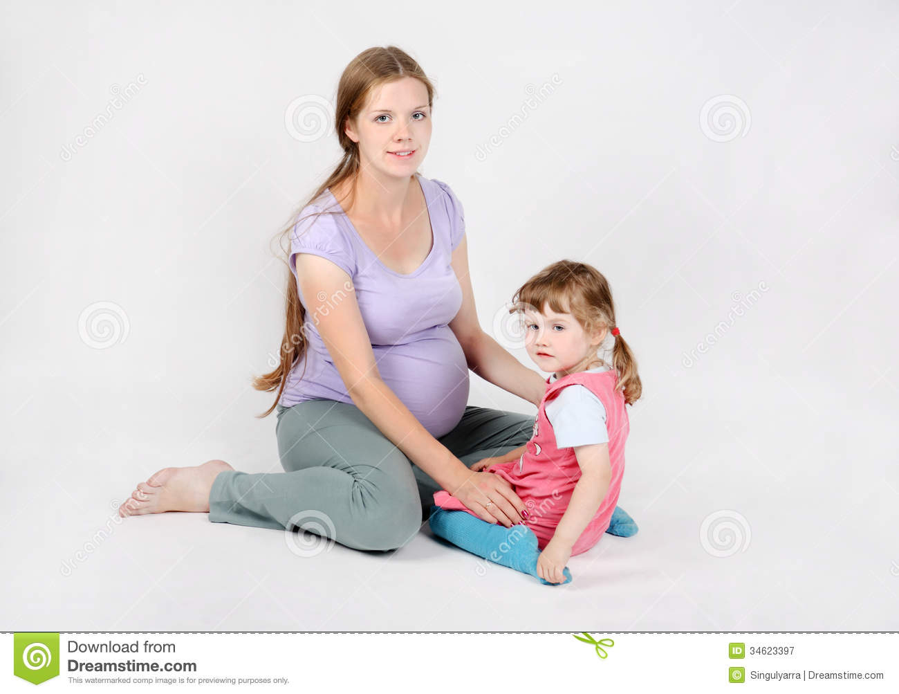 Pregnant woman sits on floor with daughter royalty free for Sitting on the floor during pregnancy