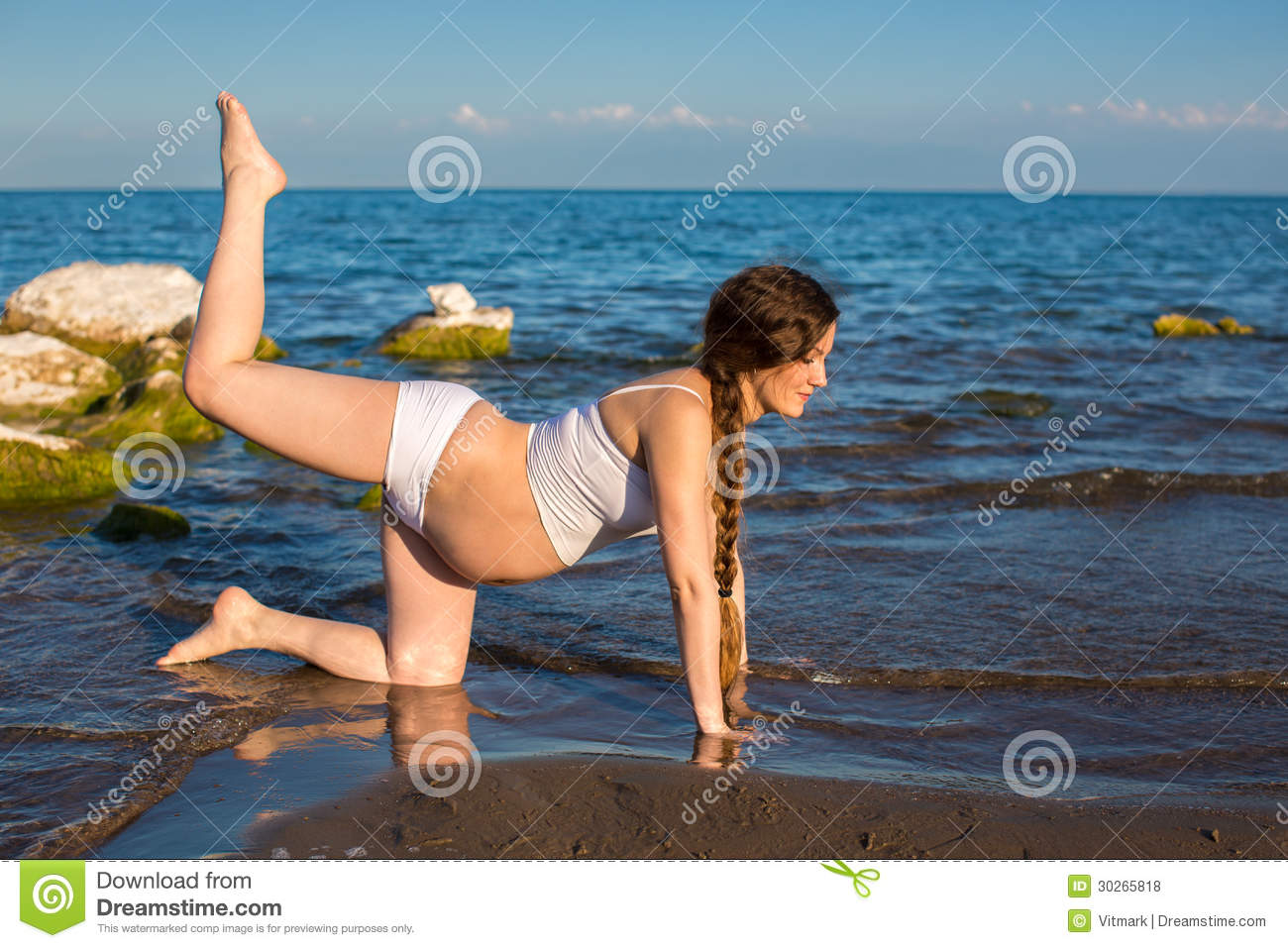 ed6864828f Pregnant woman in sports bra doing exercise in relaxation on yoga pose on  sea