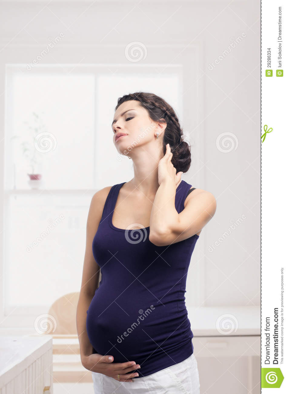Pregnant woman standing with a pain in the neck