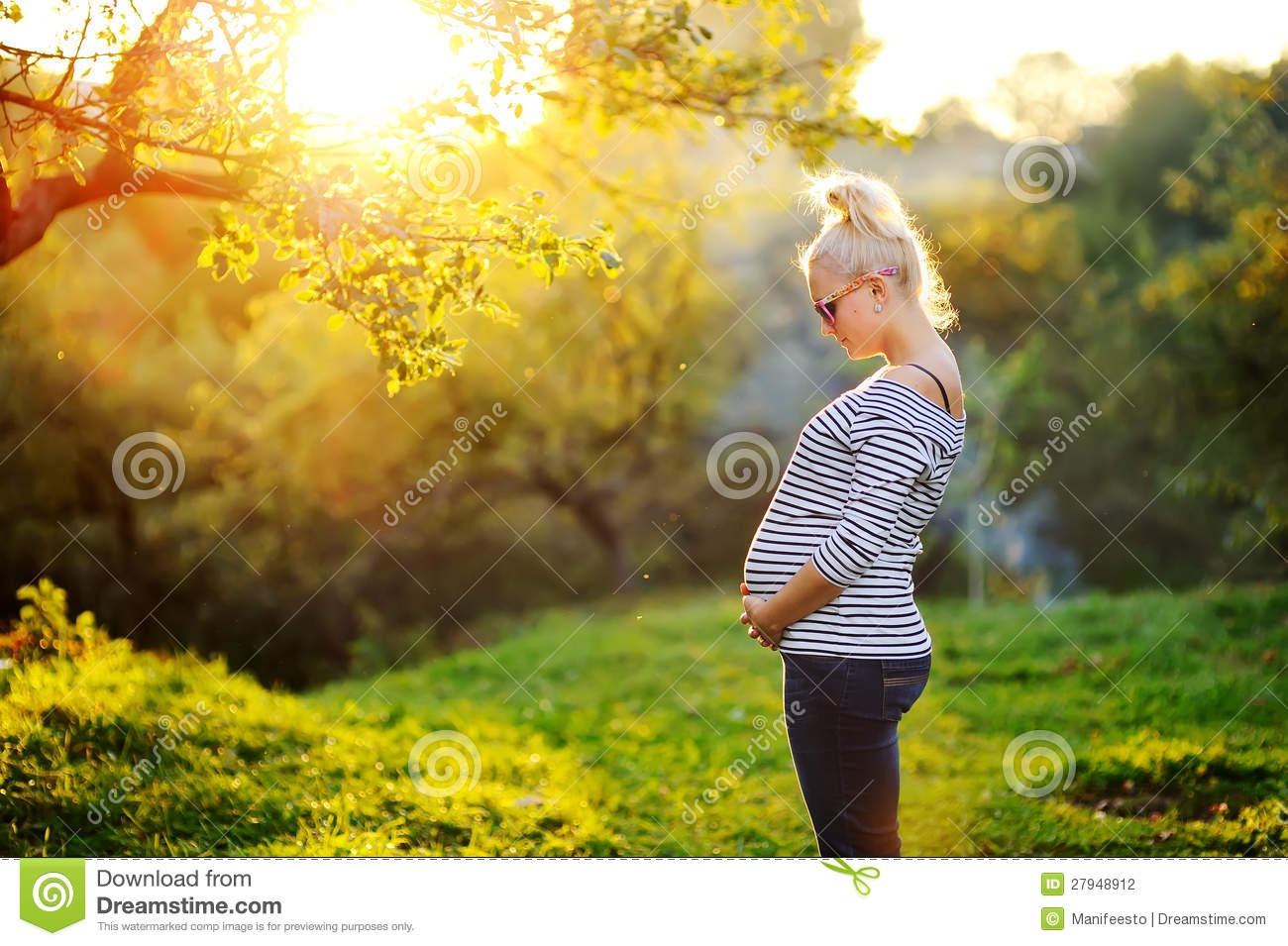 Pregnant woman stands next to the sunset stock photography for Gardening while pregnant