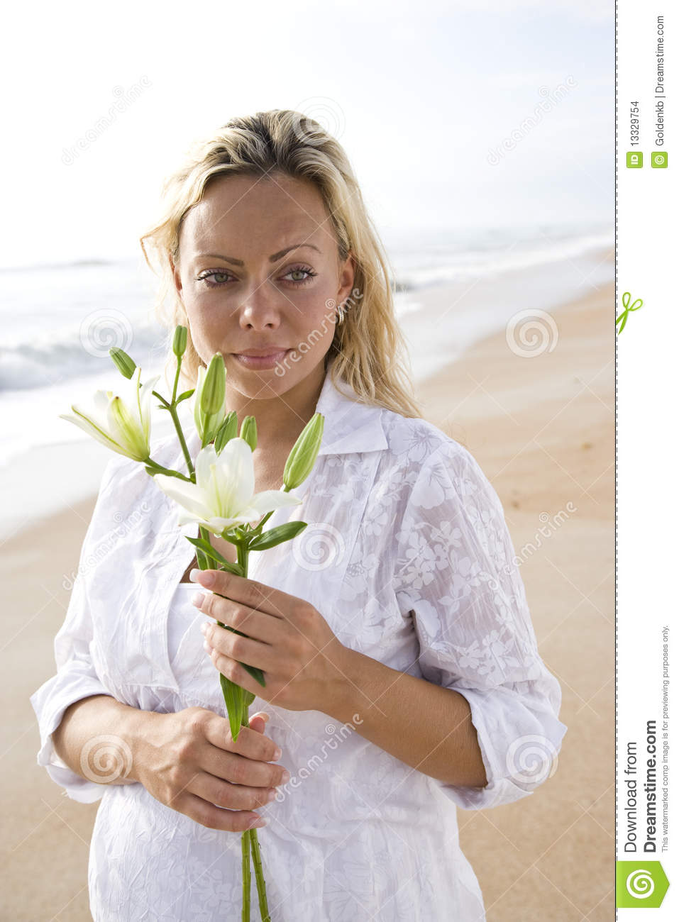 Pregnant woman in white on beach holding flower
