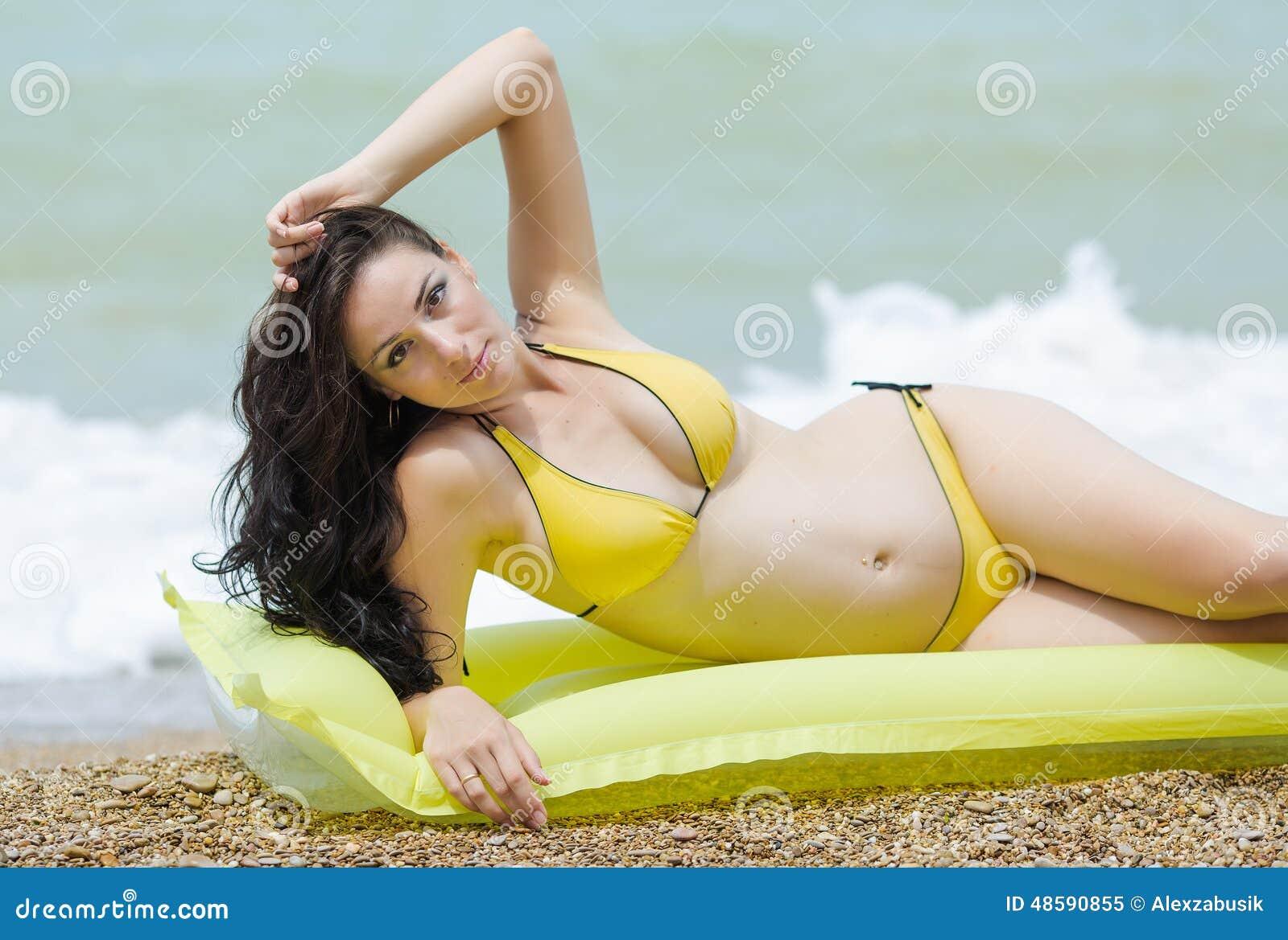 Pregnant Woman In Yellow Bikini On Pebble Beach Stock