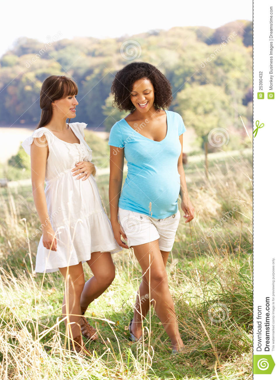 Pregnant women outdoors in countryside walking.