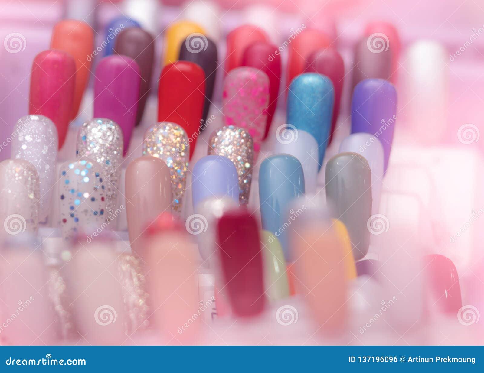 Pregos artificiais coloridos na loja do salão de beleza do prego Ajuste dos pregos falsos para que o cliente escolha a cor para o