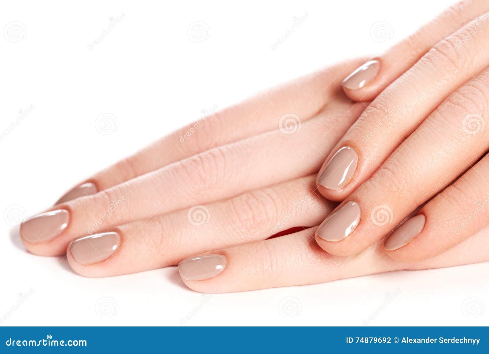 Pregos fêmeas bonitos do dedo com o close up bege do prego nas pétalas