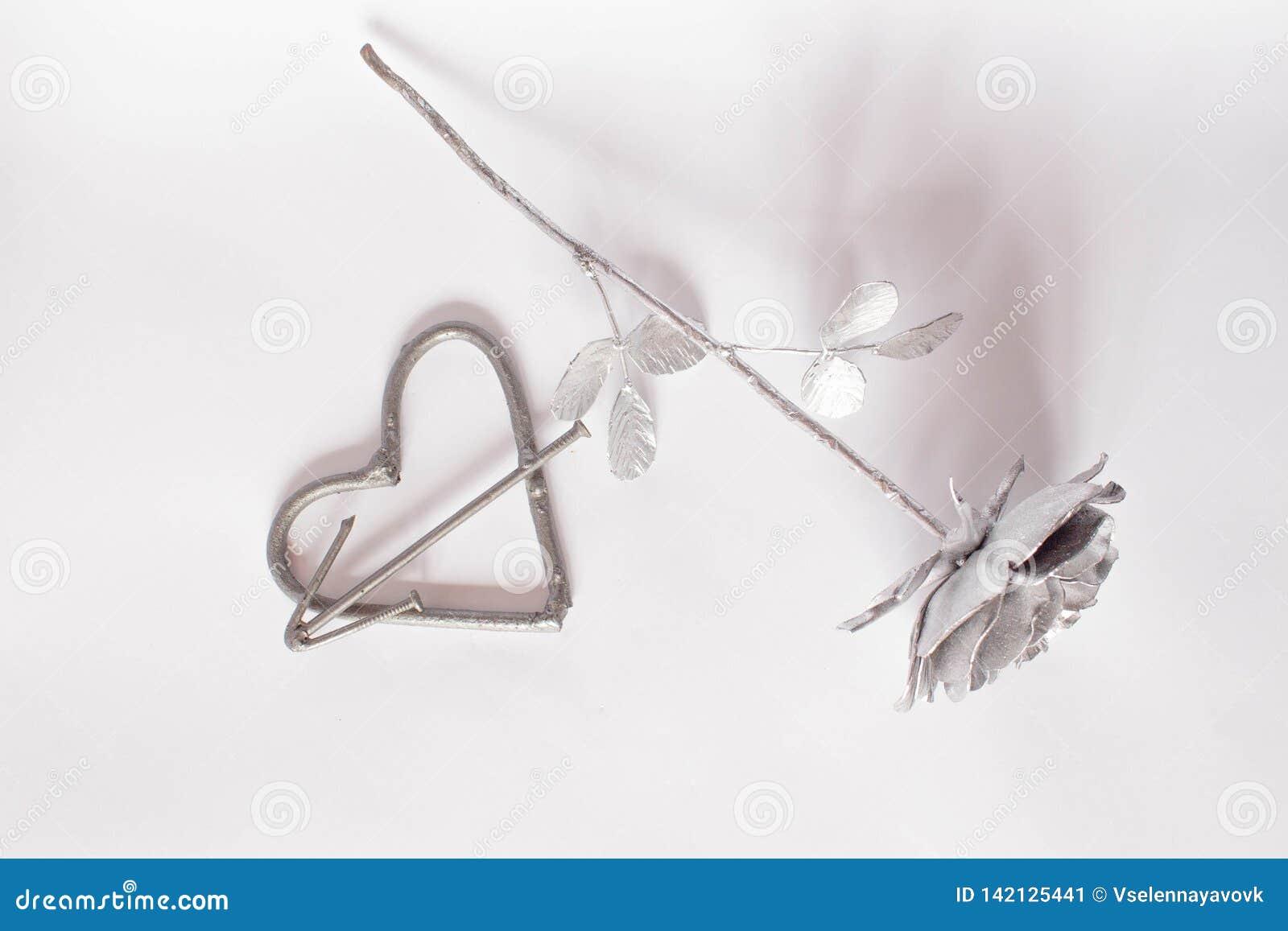 Pregos feitos a m?o forjados do metal do cora??o em um fundo branco Rosa e cora??o forjados Configura??o lisa, conceito m?nimo da
