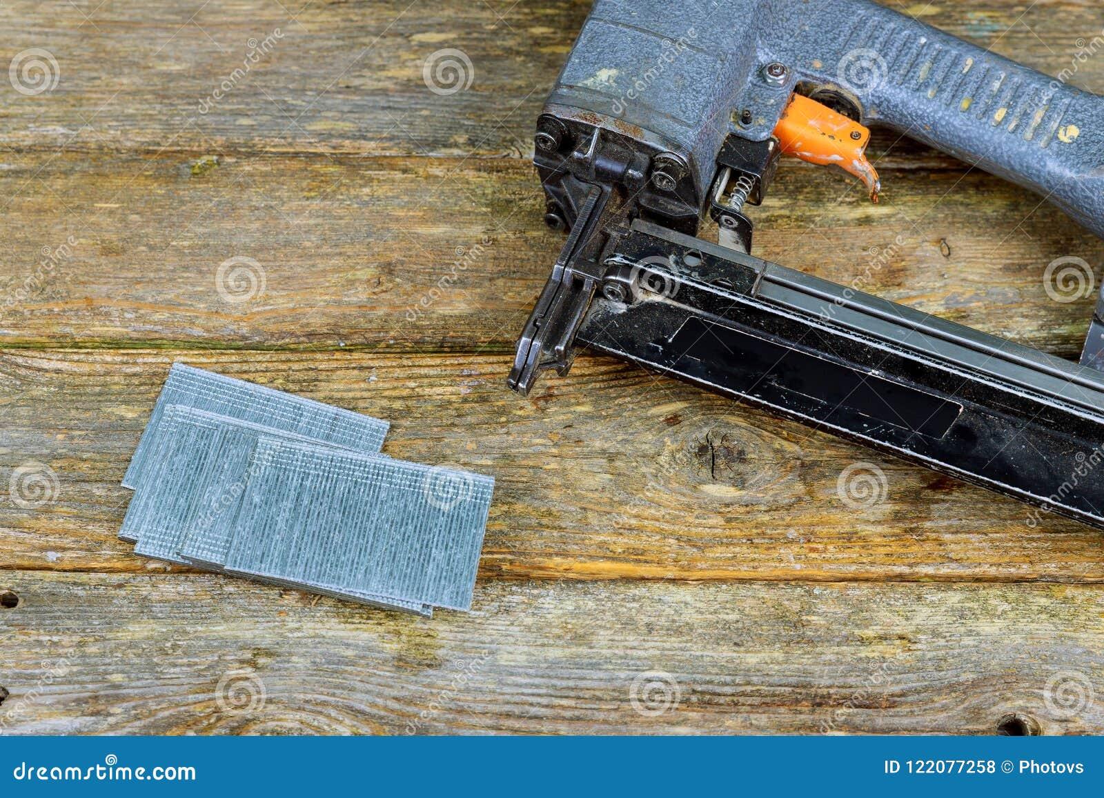 Pregue a arma e os pregos na tabela da madeira de pinho