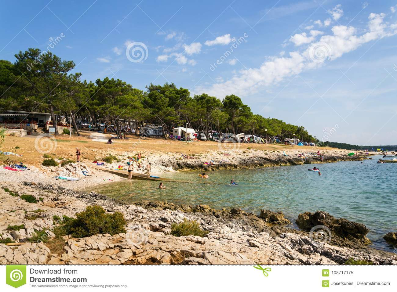 Tourists, caravans and boats on Kamenjak peninsula by the Adriatic sea in Premantura, Croatia.
