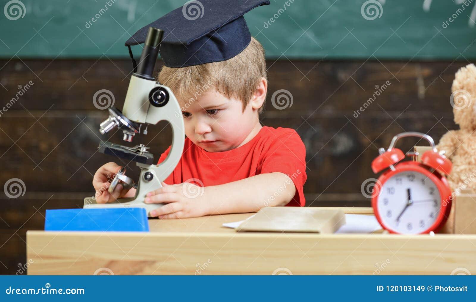 Premier ancien intéressé à étudier, apprenant, éducation Garçon d enfant dans le travail scolaire de chapeau avec le microscope d
