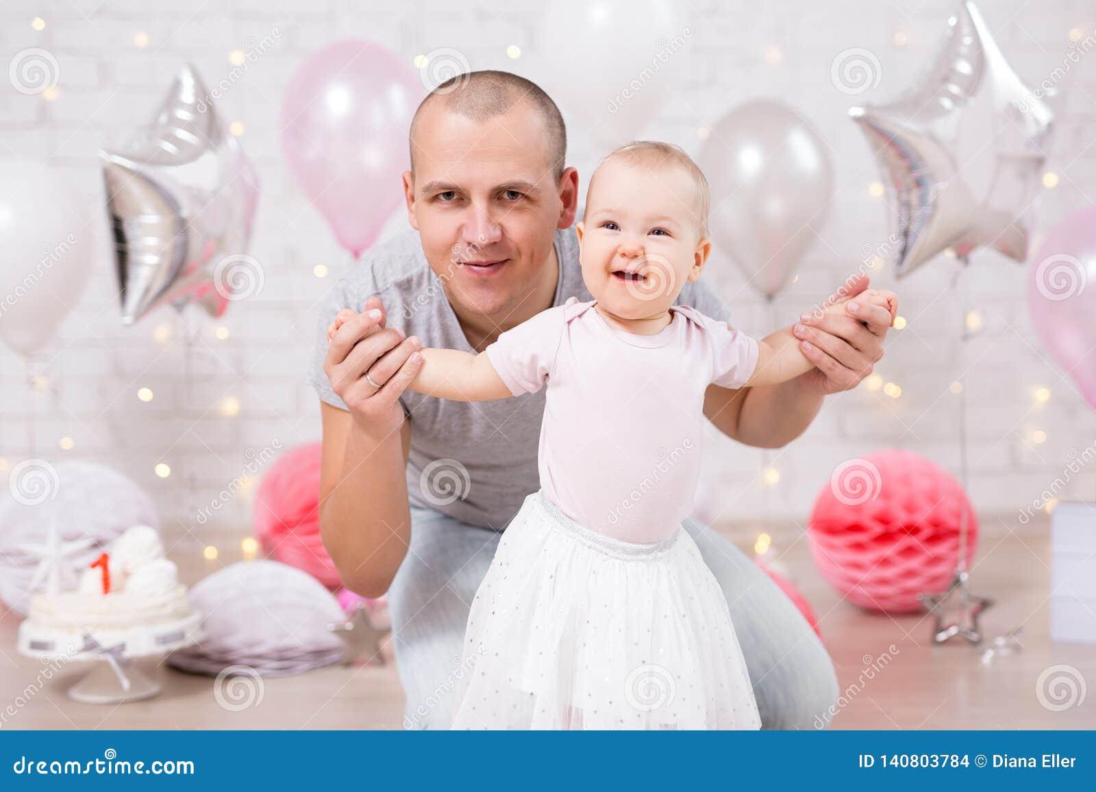 Premier concept d anniversaire - petits bébé et père mignons dans la chambre décorée avec le gâteau et les ballons