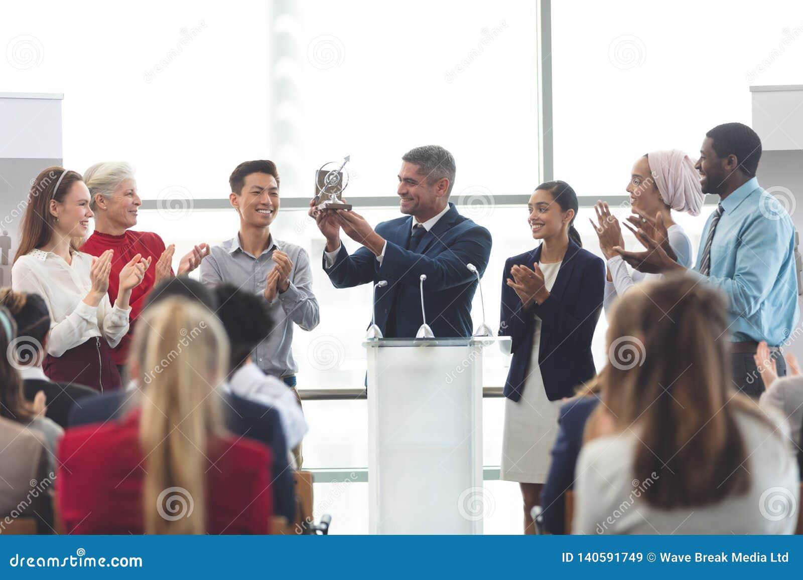 Premio della tenuta dell uomo d affari al podio con i colleghi in un seminario di affari