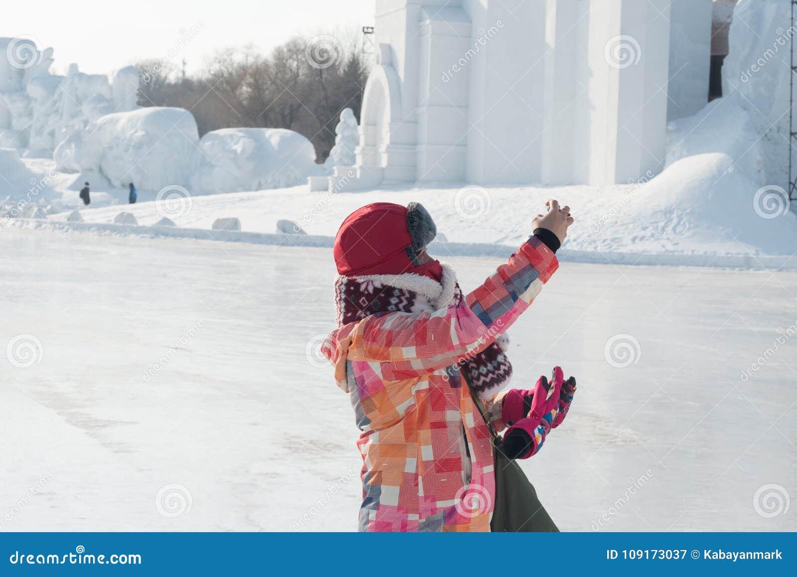 Prenant des selfies - la femme a tendu la main prenant la photo au froid de congélation de festival de neige de Harbin