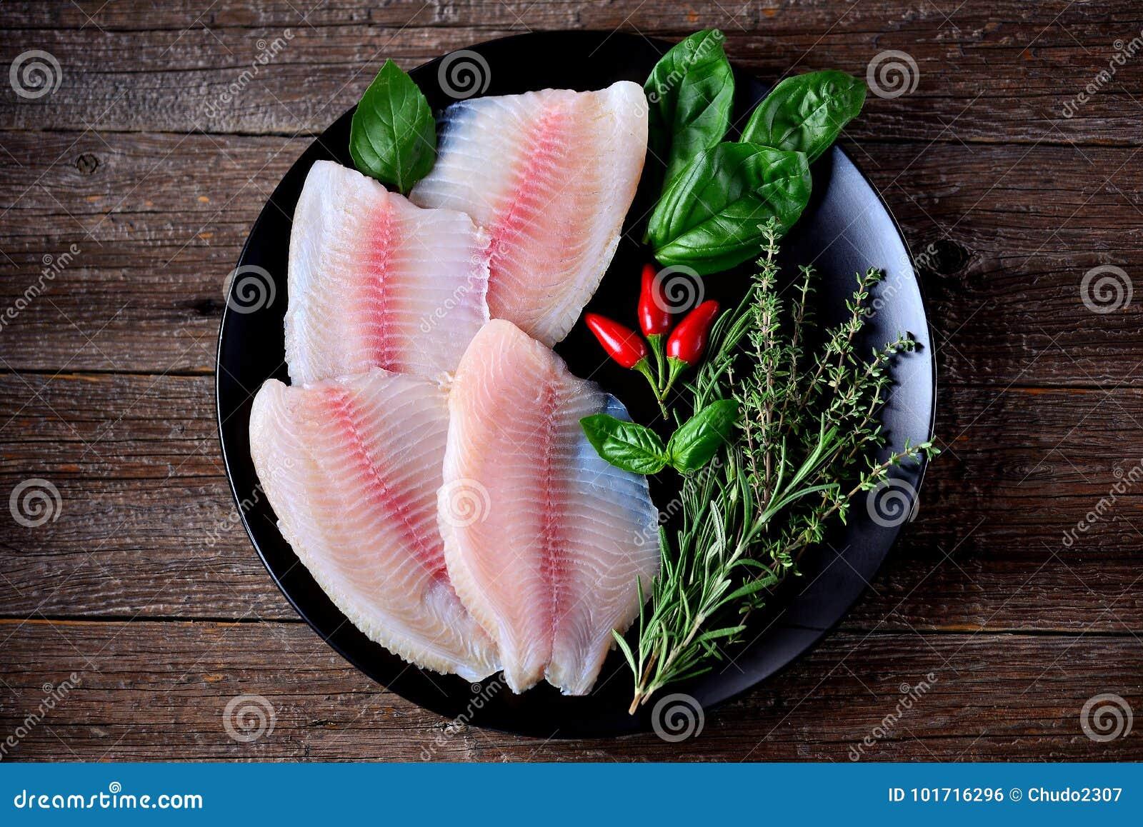 Prendedero crudo fresco de los pescados de la Tilapia con pimienta del tomillo, del romero, de la albahaca y de chile