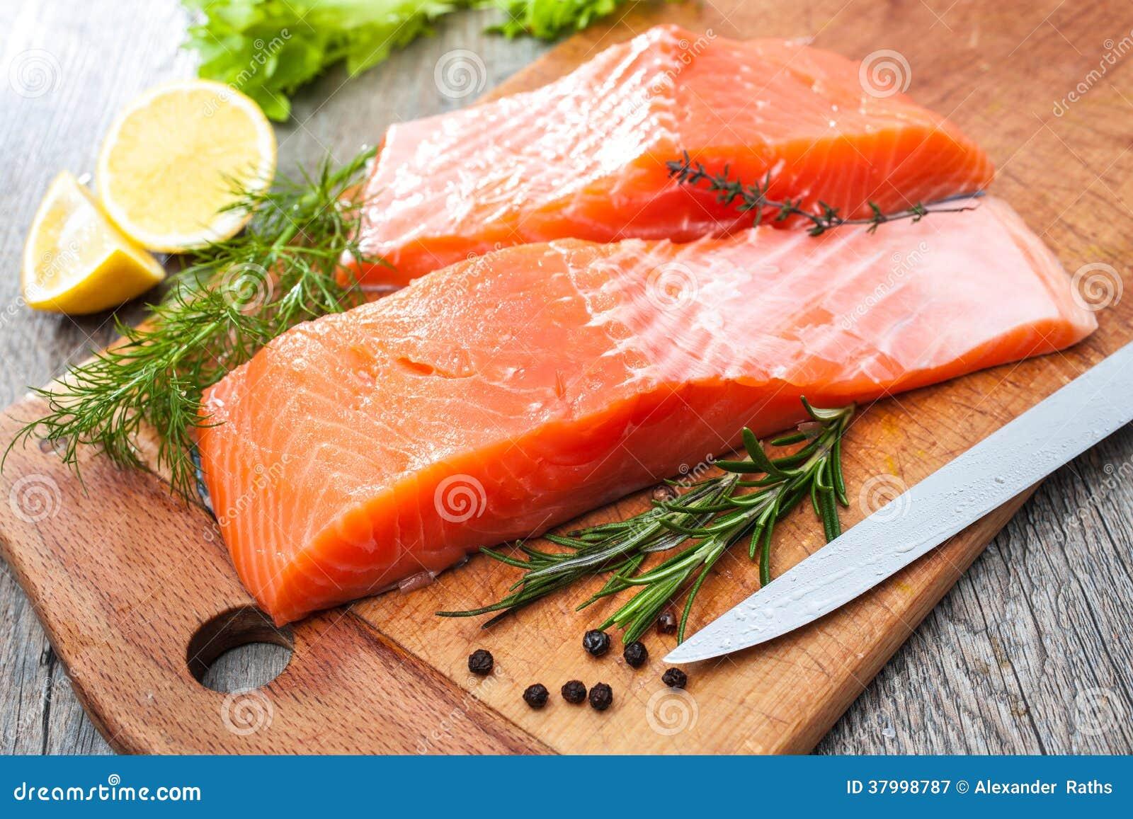 Prendedero de pescados de color salmón crudo con las hierbas frescas