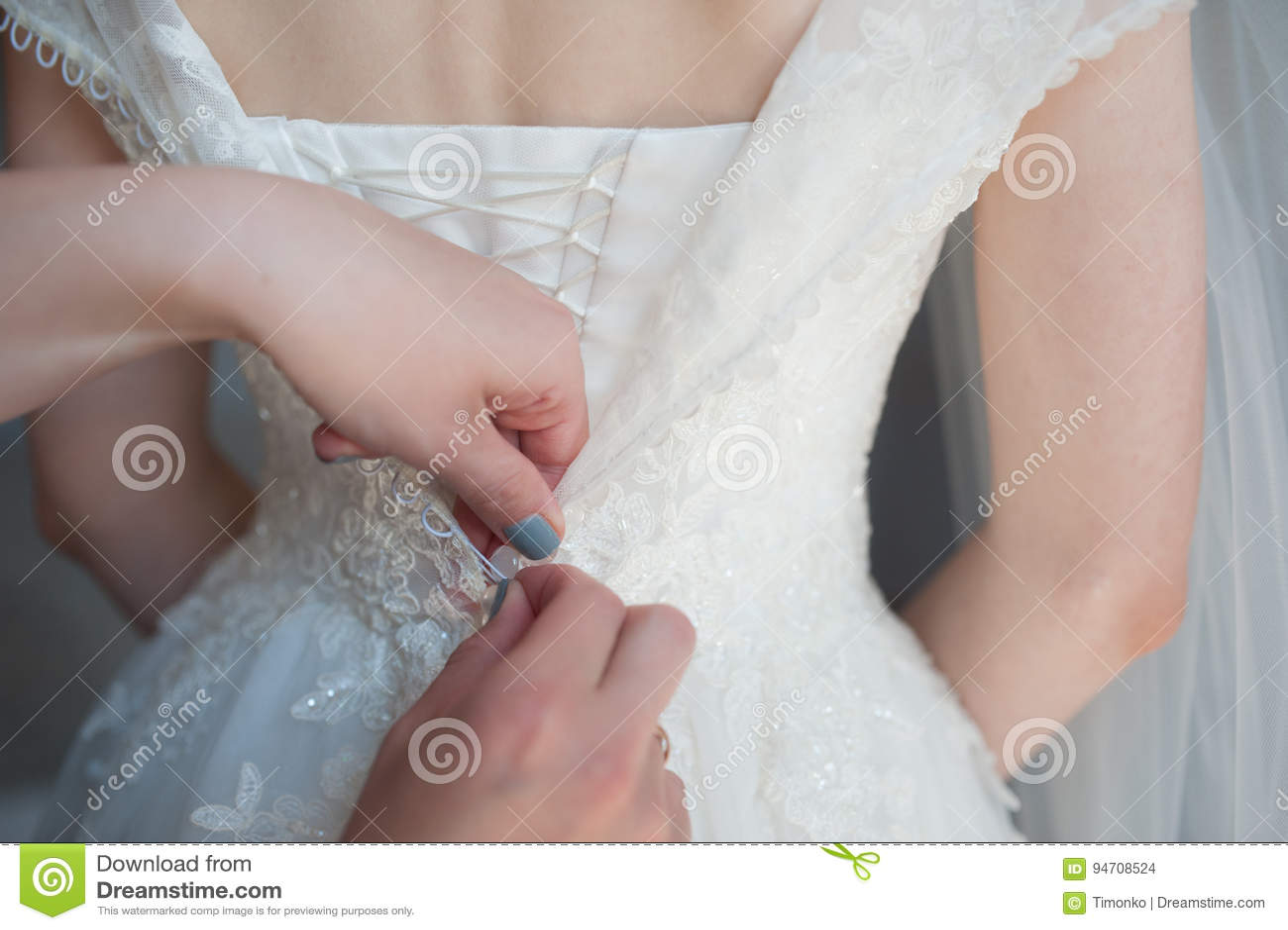 Prendendo o vestido, asseguração no vestido do ` s da noiva, taxas do botão do ` s da noiva, vestido de casamento