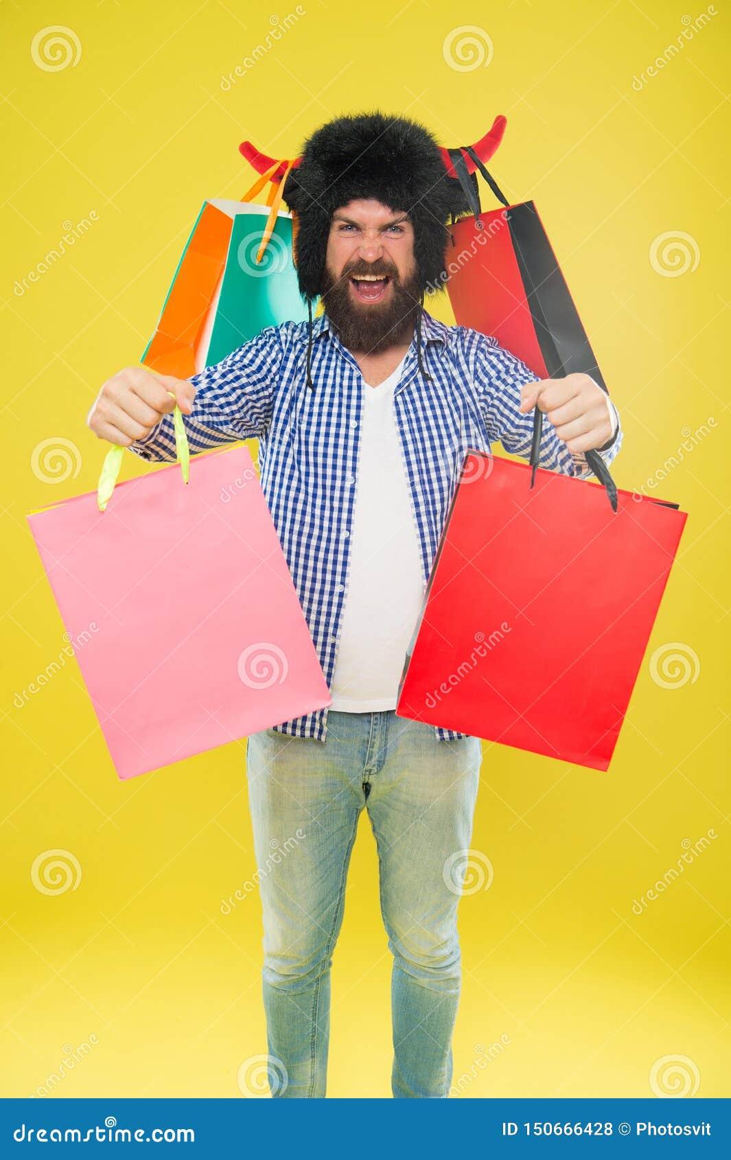 Prenez les sacs, son Black Friday Hippie heureux dans le chapeau de klaxons de taureau tenant des sacs ? provisions Homme barbu s