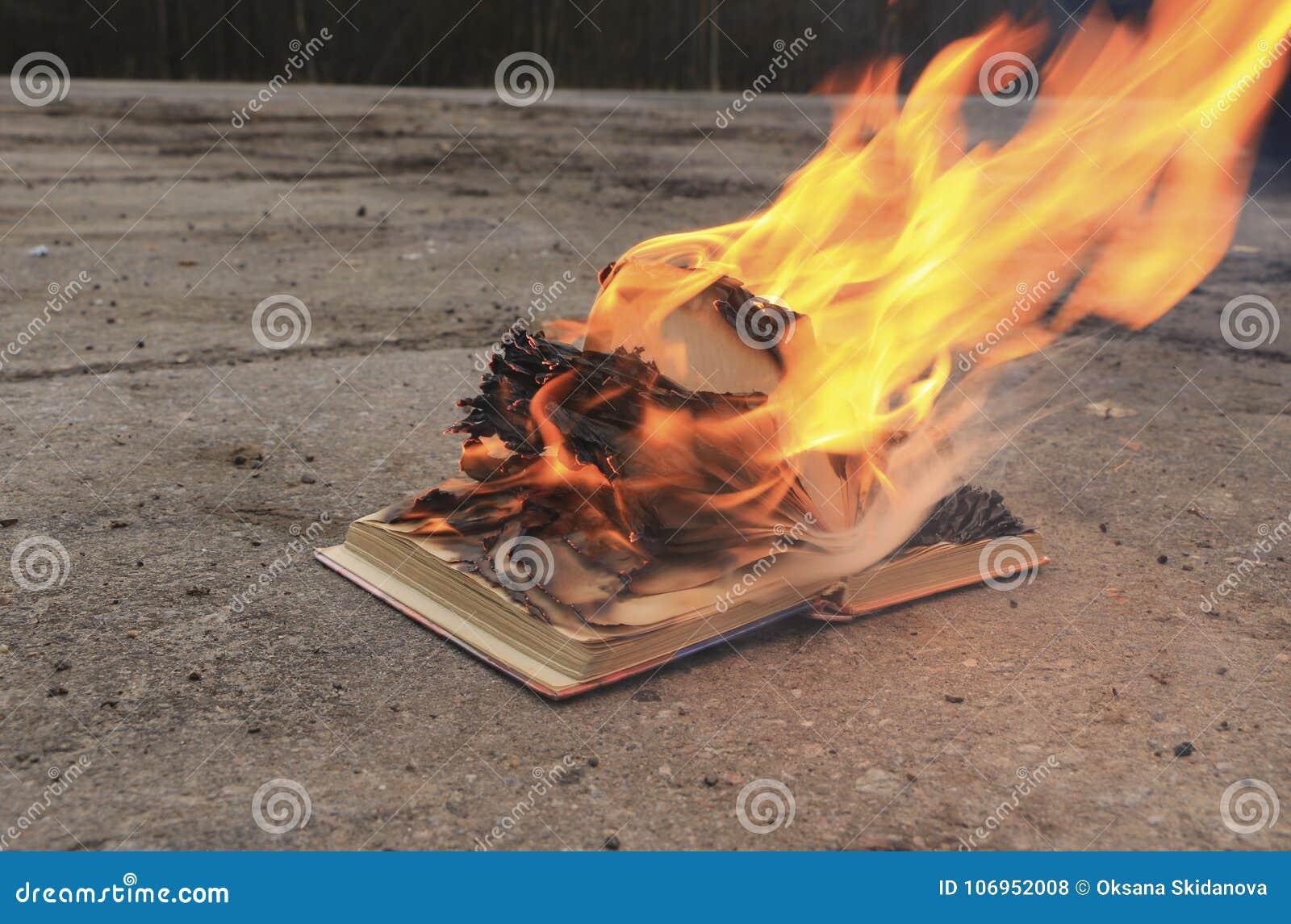 Prenoti con le pagine brucianti su una superficie di calcestruzzo