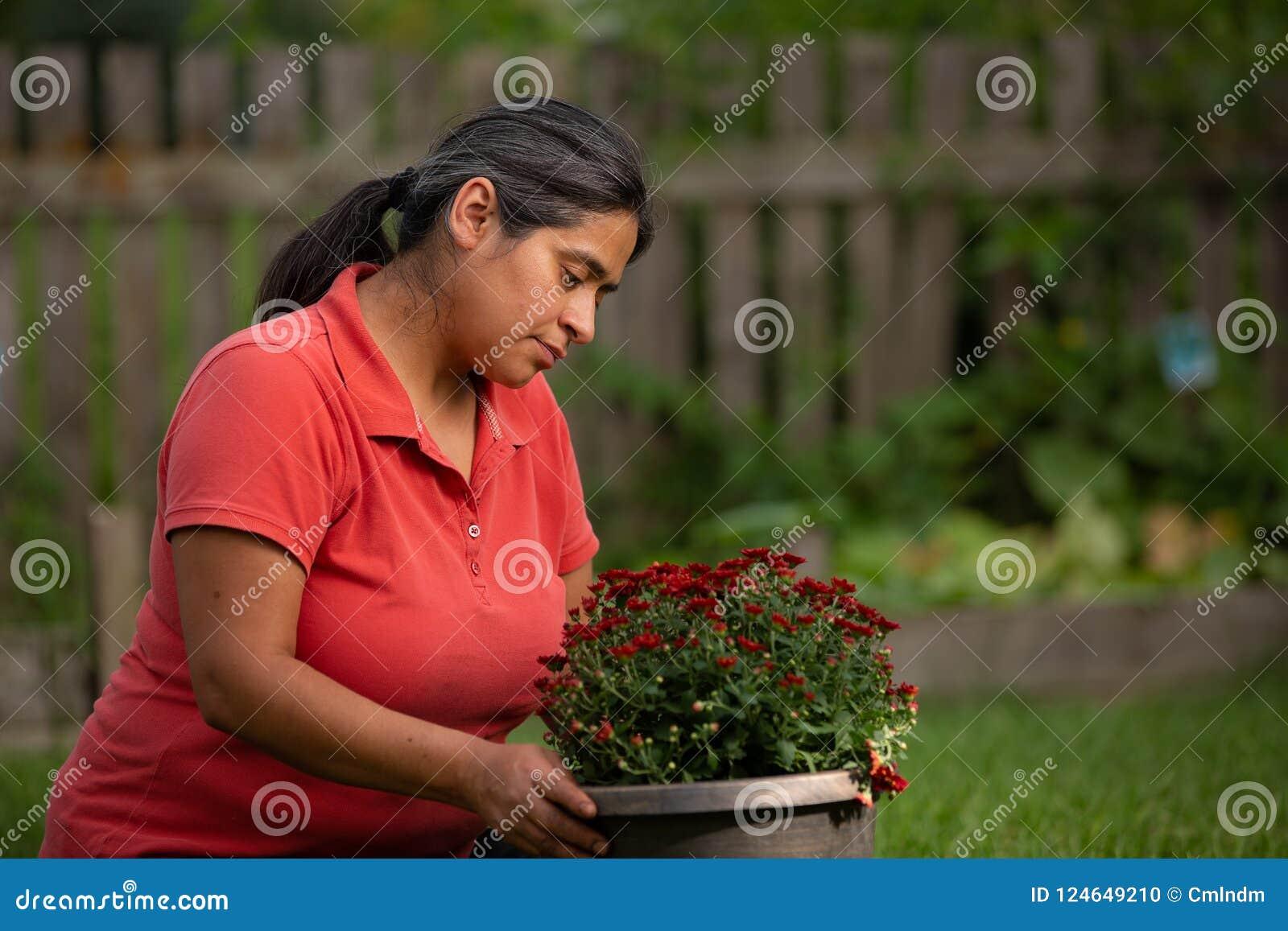 Preoccuparsi di lavoro della donna ispana per i suoi fiori