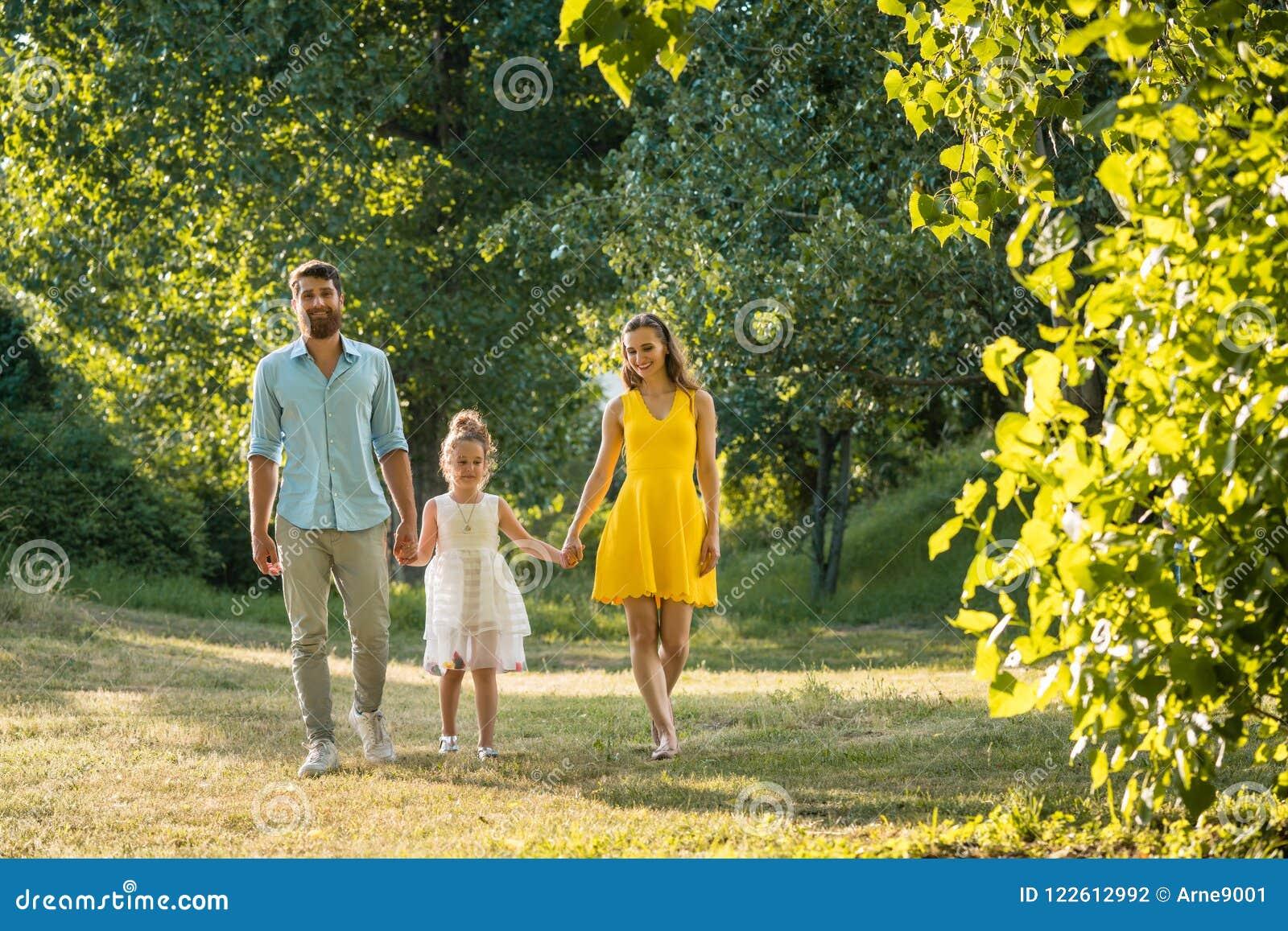 Preoccuparsi parents tenersi per mano della figlia mentre cammina insieme
