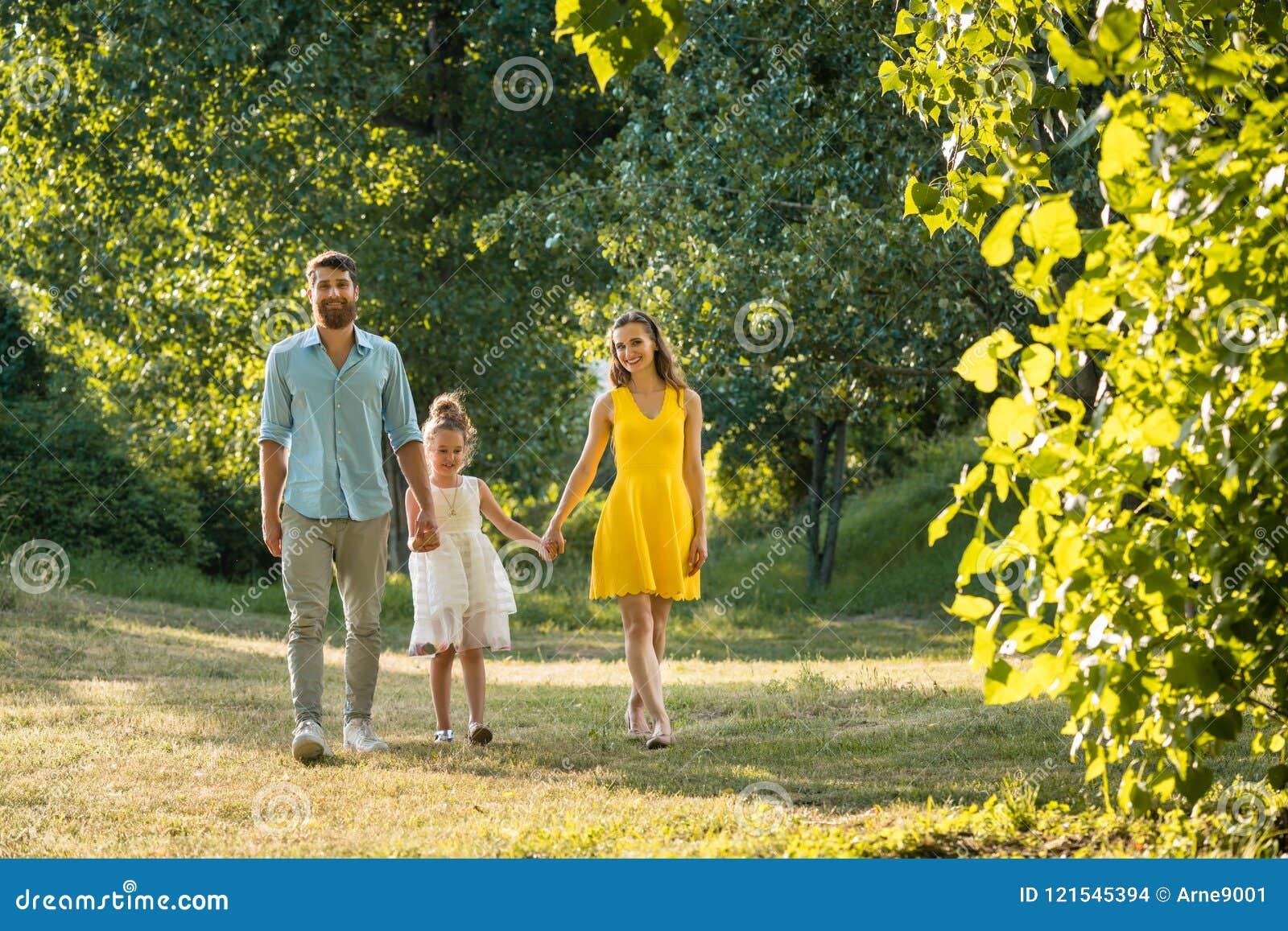 Preoccuparsi parents tenersi per mano della figlia mentre cammina insieme nel parco