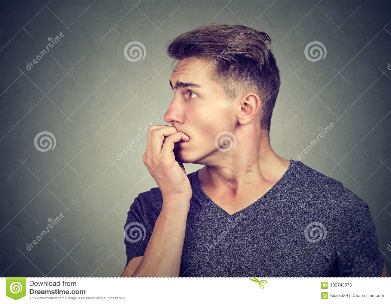 Preoccupied anxious young man biting his fingernails looking to the side